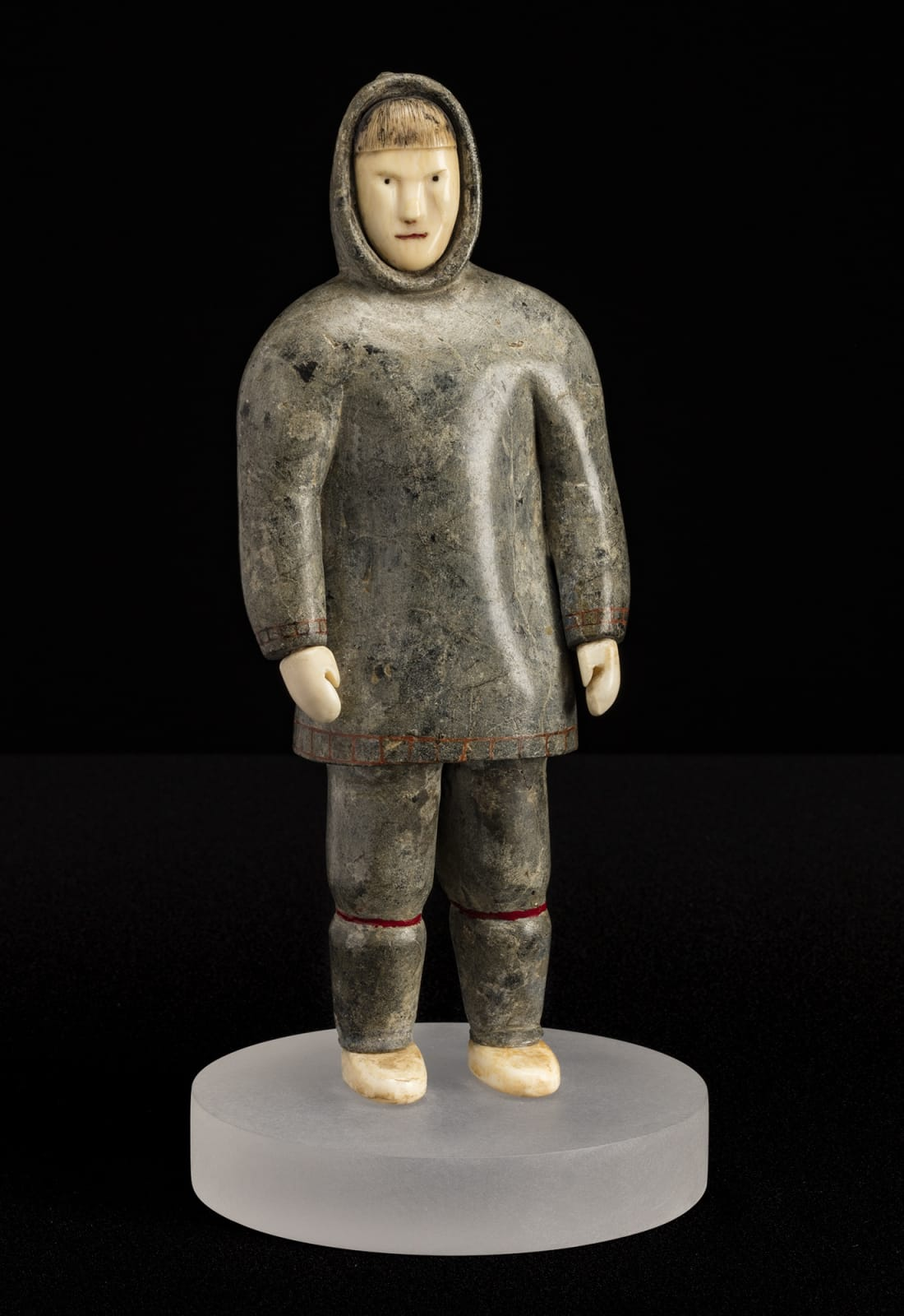 Lot 89 Possibly SHEOKJUK OQUTAQ (1920-1982) m., KIMMIRUT / KINNGAIT (LAKE HARBOUR / CAPE DORSET) Standing Man, mid 1950s stone, ivory, red inlay, and black colouring, 9.75 x 3.75 x 2.5 in (24.8 x 9.5 x 6.3 cm) not including lucite base Estimate: $4,500— $6,500