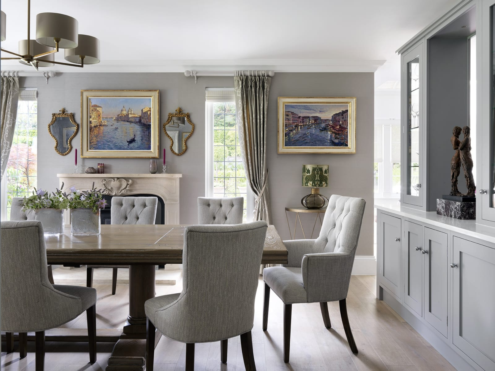 Contemporary Venetian paintings sit well in this neutral dining room scheme