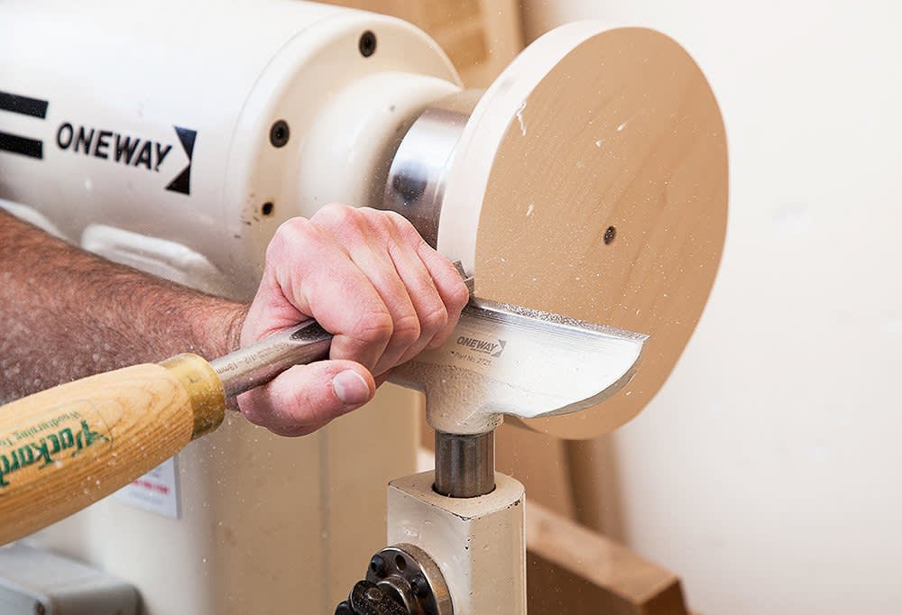 A craftsman carves a beautiful wood base