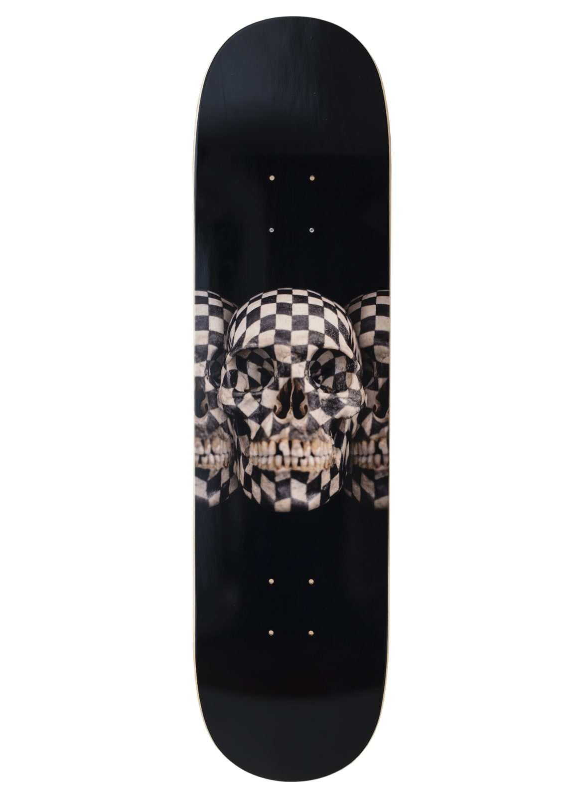 A board of a black skateboard designed with a set of checkered skulls in the center.