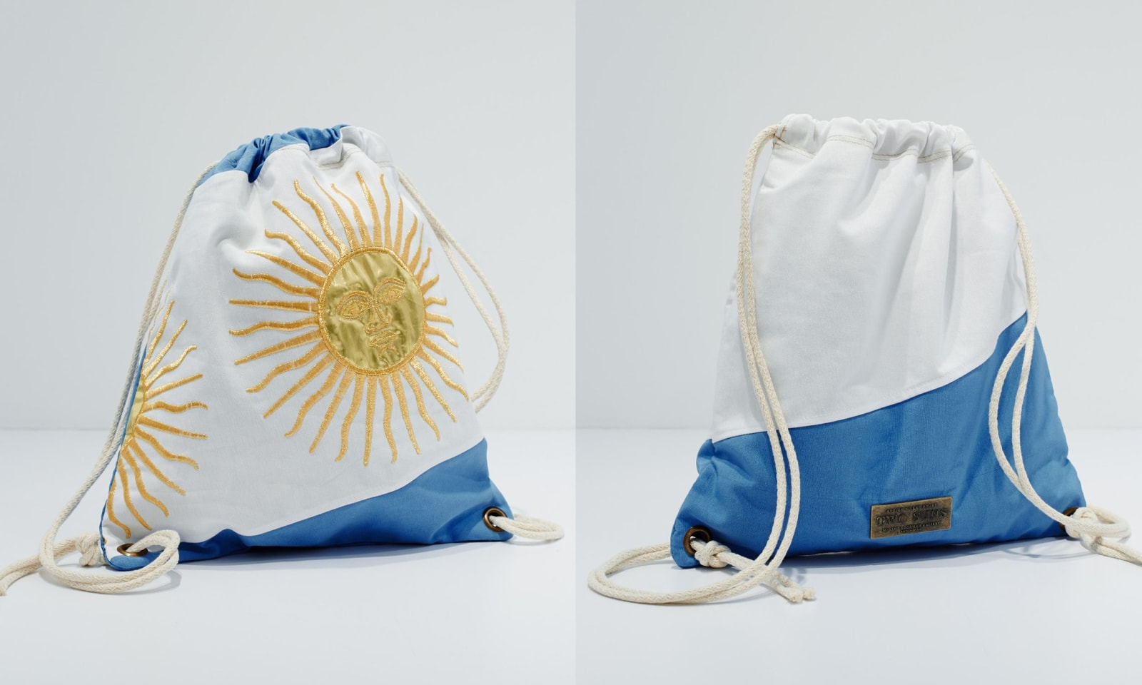 Blue and white drawstring bag with embroidered sun design by Adrian Villar Rojas.