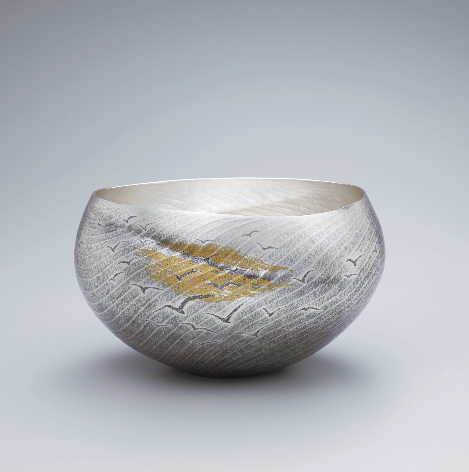 "Osumi Yukie (b. 1945), Living National Treasure Silver Vase ""Kaikei"" (Seascape), 2019 Hammered silver with nunomezogan (textile imprint inlay) decoration in lead and gold h. 7 7/8 x w. 13 5/8 x d. 12 5/8 in. (20 x 34.5 x 32 cm)"