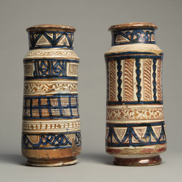 """<span class=""""title""""><em>Two slender albarelli decorated with trelliswork, tendrils, and pseudo-Kufic motifs</em>, c. 1400 - 30</span>"""