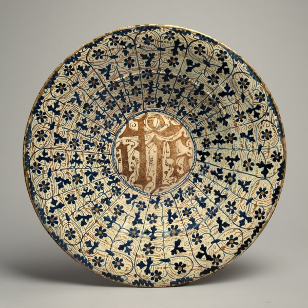 """<span class=""""title""""><em>A large lustreware charger emblazoned with 'IHS' among parsley leaves and bryony flowers</em>, c. 1430-60</span>"""