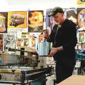 Portrait of artist Chuck Sperry mixing ink in the studio