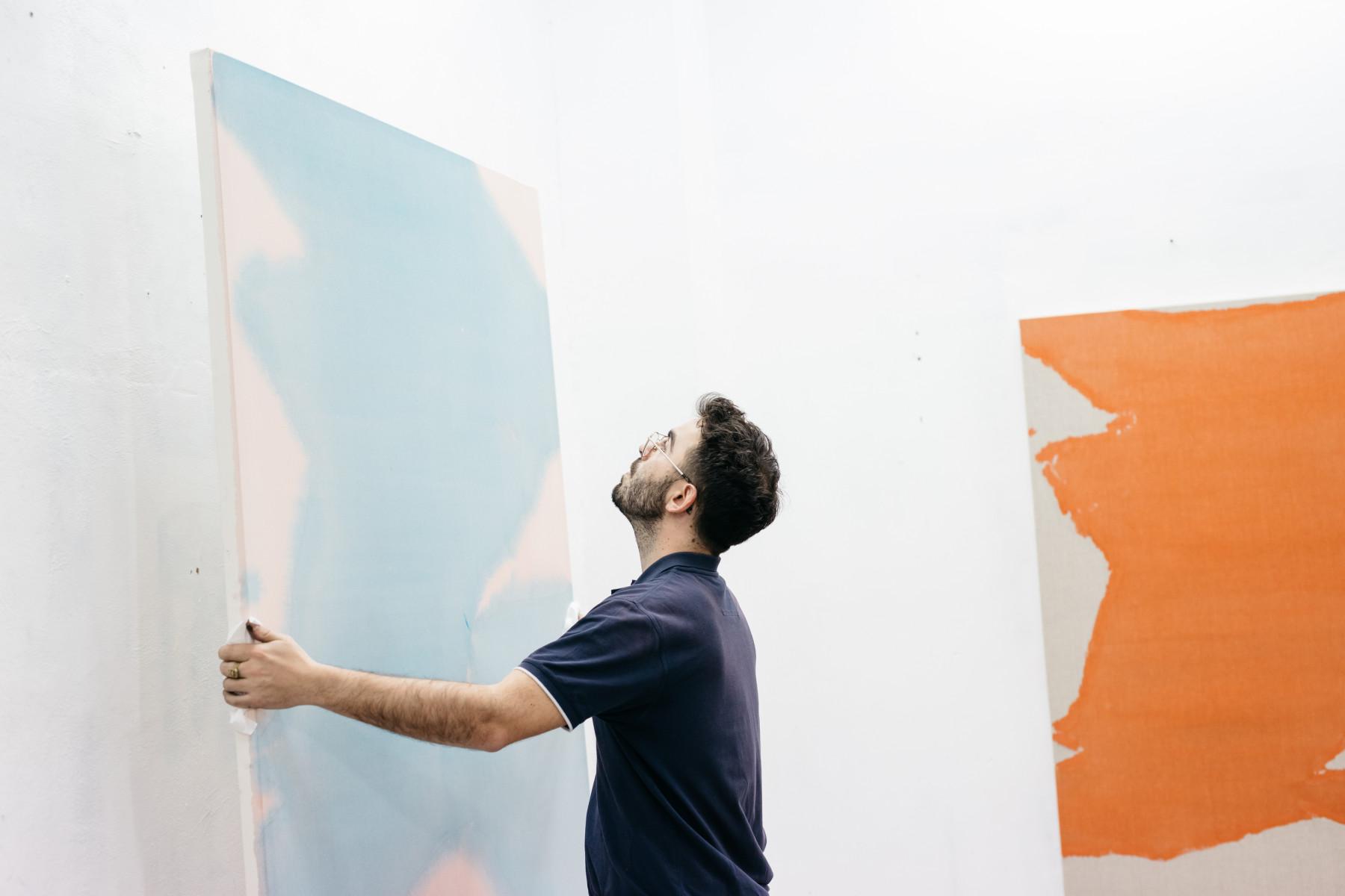 Man putting up artwork