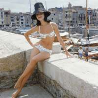 Photographed for the January 1961 issue of LIFE, Christine Mayer poses on the jetty overlooking St. Tropez harbor wearing the year's biggest Riviera hit, an embroidered organdy bikini designed by Andejo of Nice