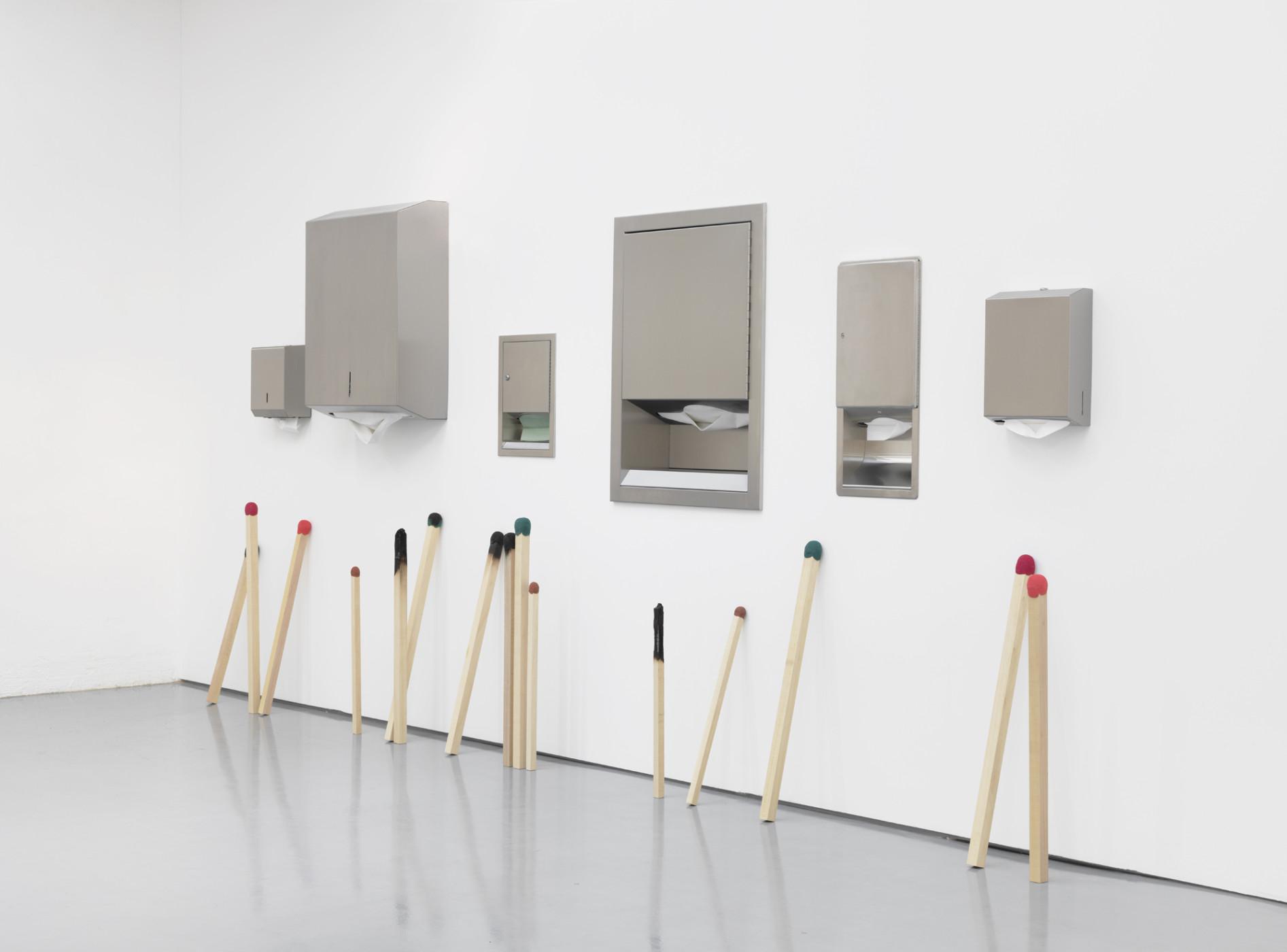 "<div class=""title""><em>Waiting, Giving, Spent</em>, 2012</div><div class=""medium"">brushed steel paper towel dispensers, paper towels, wooden matchsticks</div><div class=""dimensions"">201.0 x 435.0 x 28.0 cm<br />79 1/8 x 171 1/4 x 11 in.</div>"
