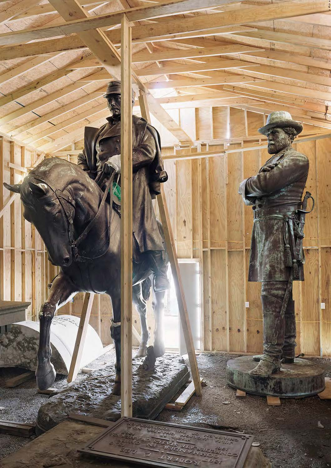 Two statues, one of a man and a man on a horse, stand in a plywood shed.