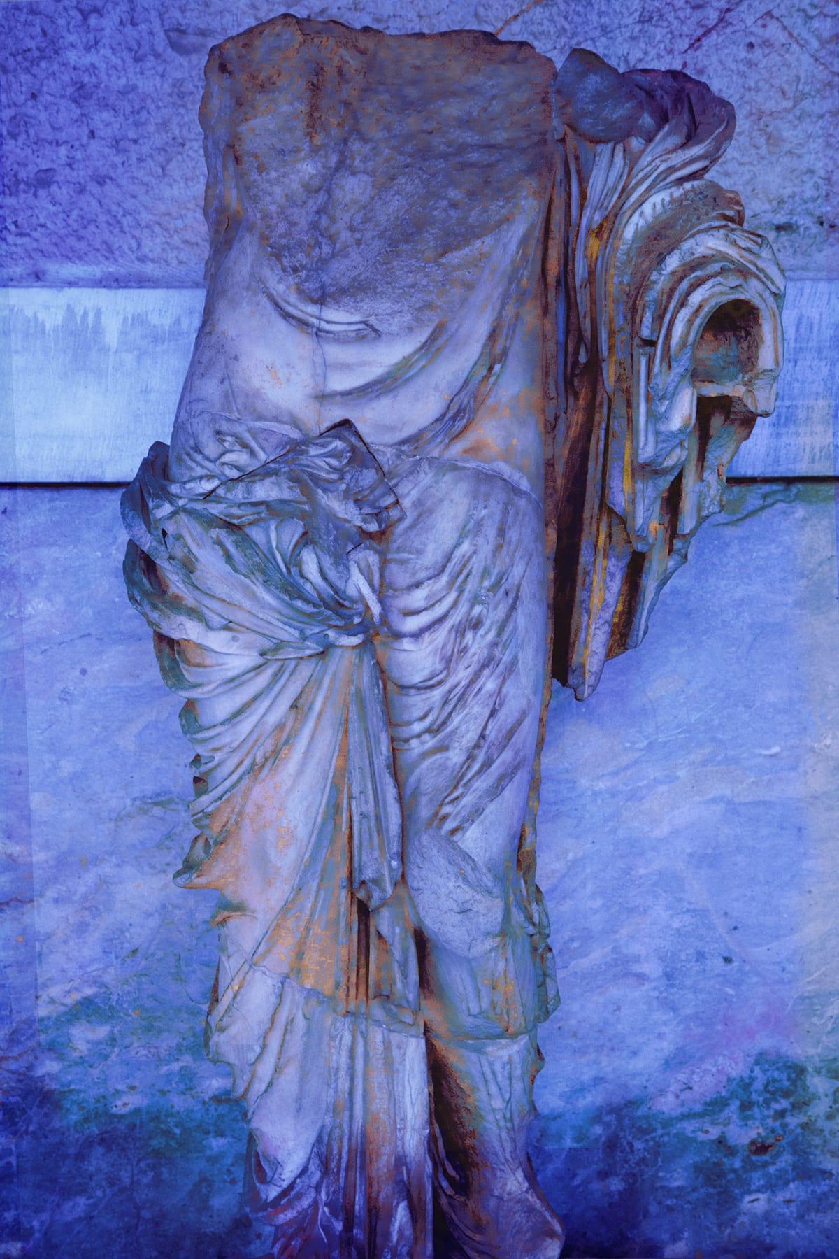 A headless statue of a draped male in blue and aqua light