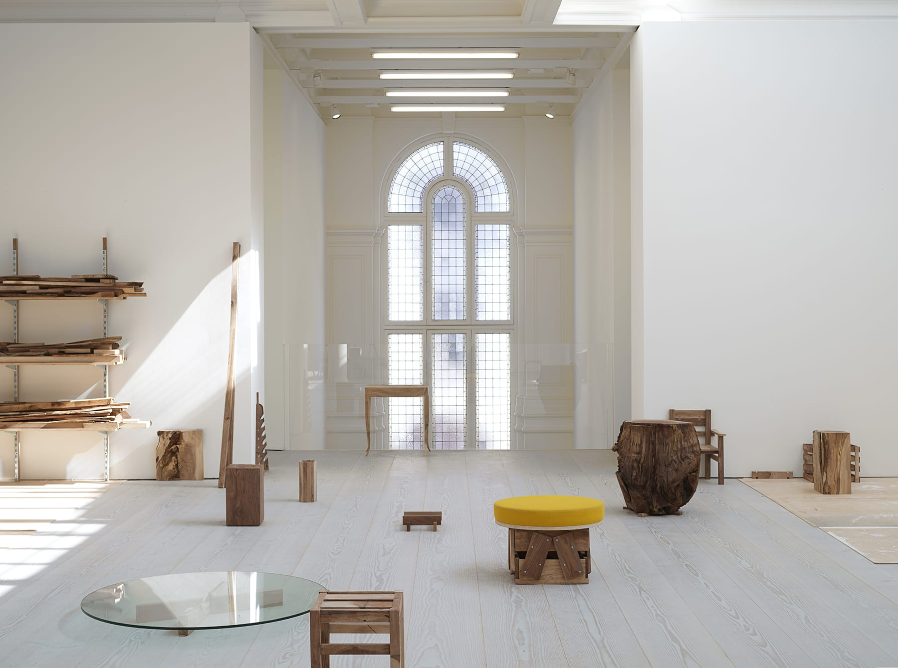 A gallery room with a floor-to-ceiling glass window that faces several wooden coffee tables and a flat, round glass circular structure on the ground.