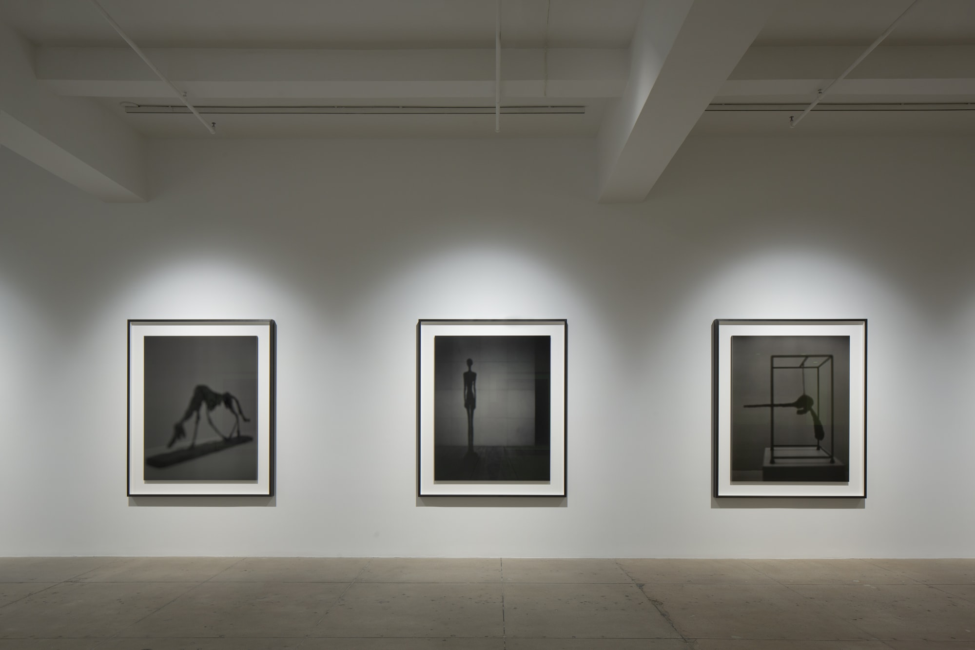 Gallery view of three black and white photos of art objects from a museum on a wall.