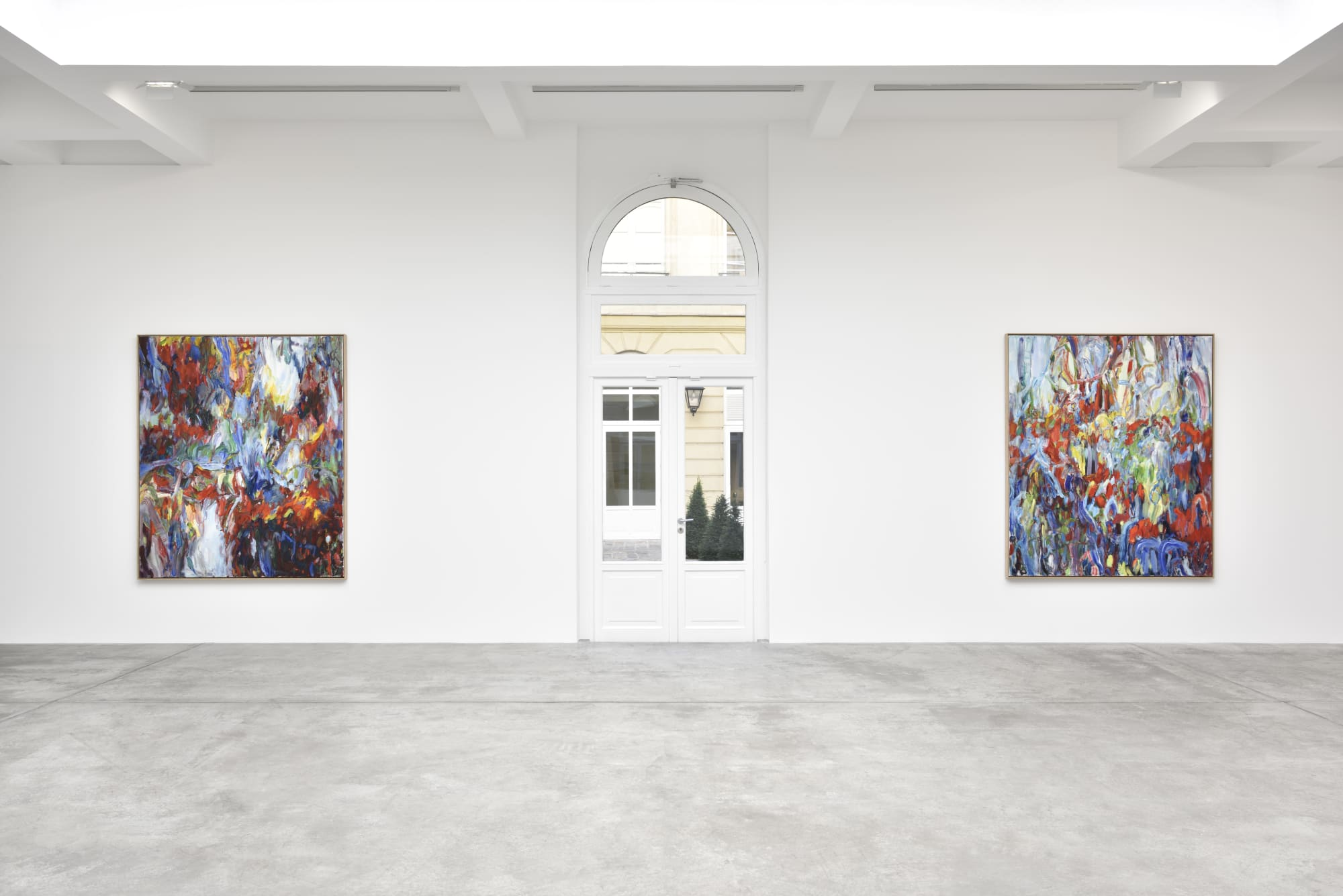 Gallery view of two colorful abstract paintings by Sabine Mortiz on either side of a doorway.