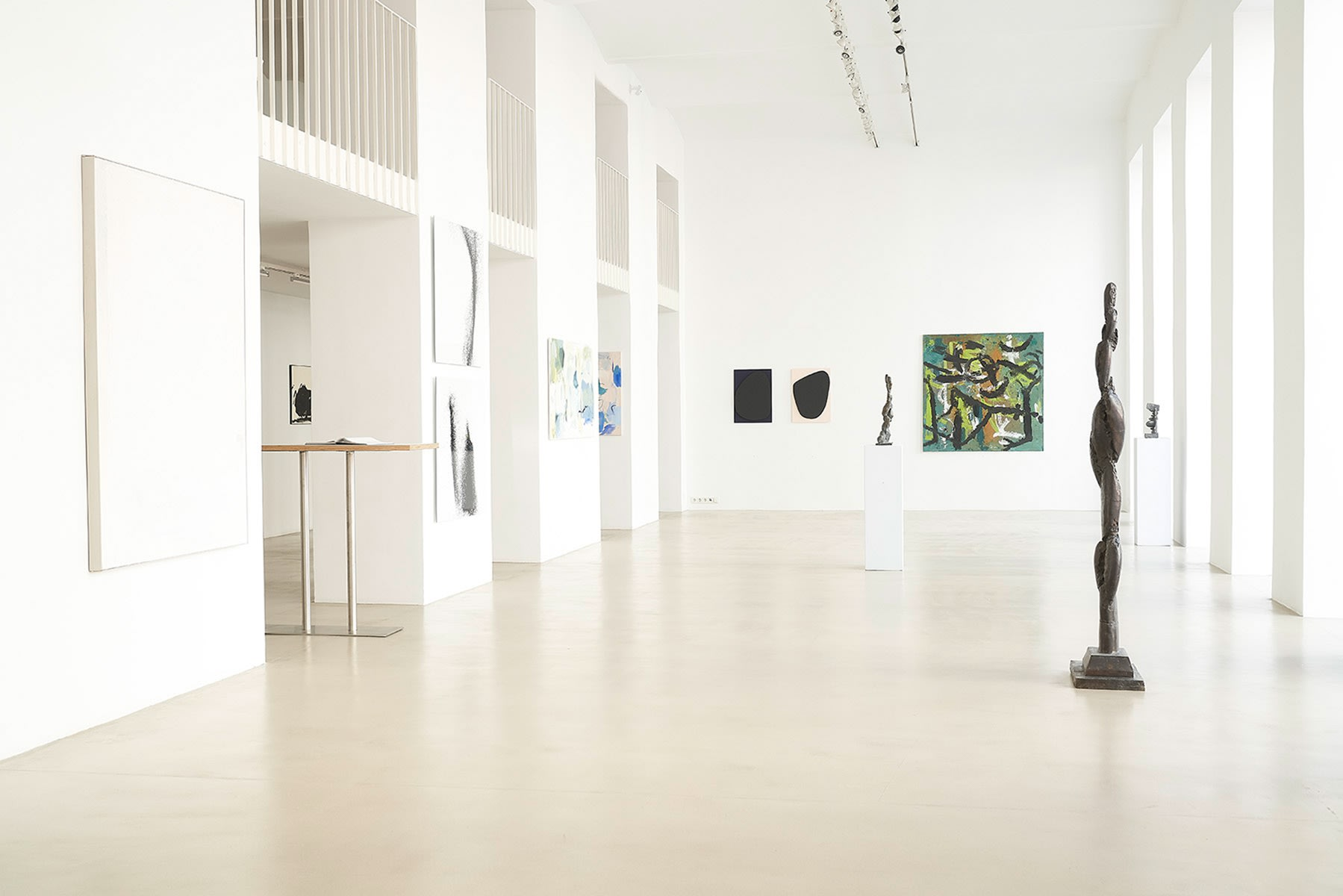 ZS Art Gallery shows the gallery space with its high white walls and a mezzanine with balcony showing artworks from various artists