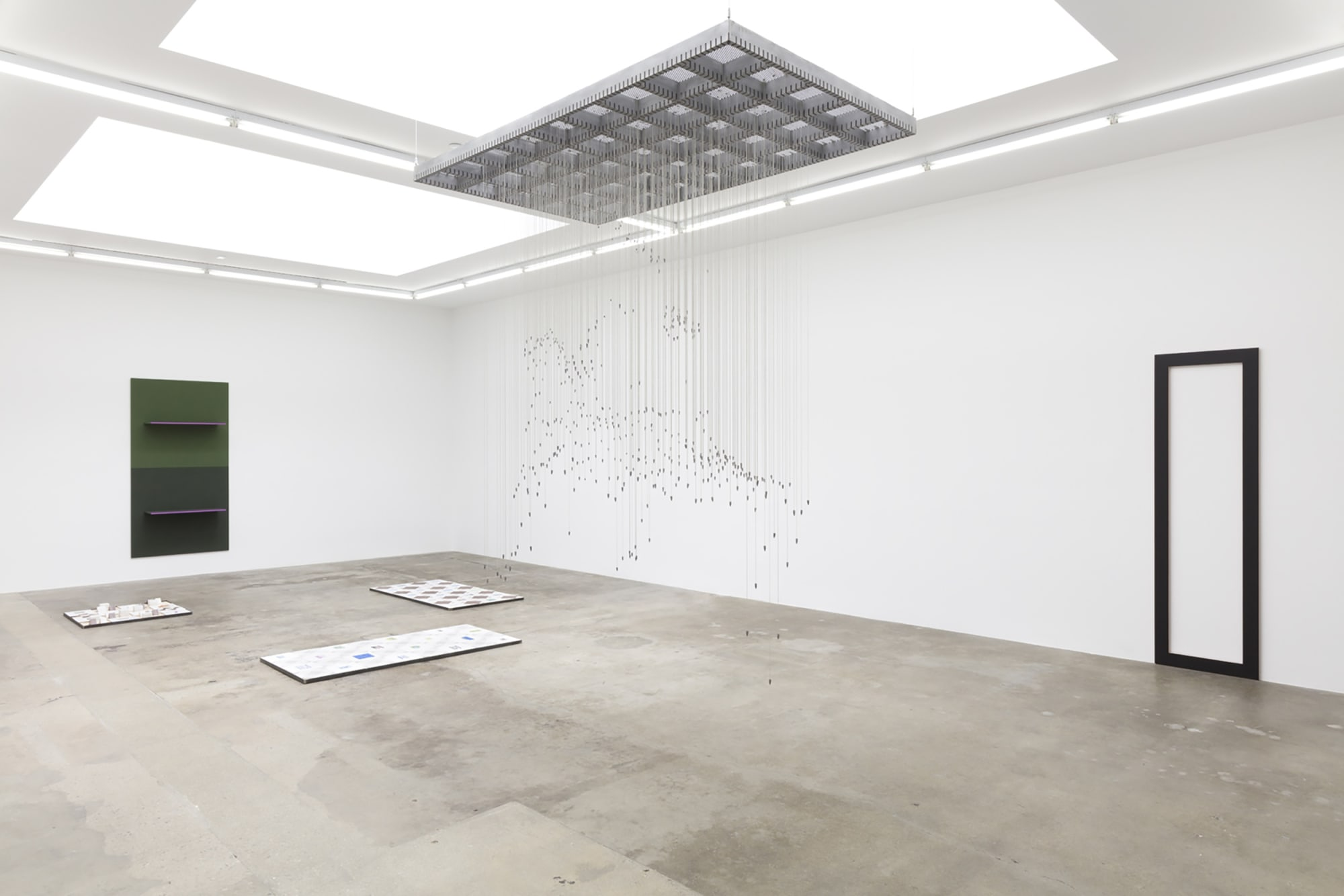 Installation image of spindly Sean Townley sculpture hanging from ceiling, Lisa Williams sculptures on walls behind it, and Michael Queenland sculptures installed on the polished concrete floor