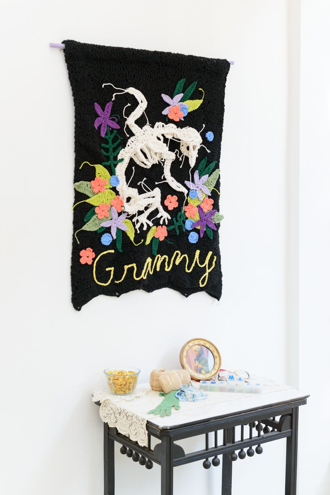 Crocheted GRANNY banner with animal skeleton and flowers by Caitlin McCormack above small installation featuring objects from grandma's nightstand