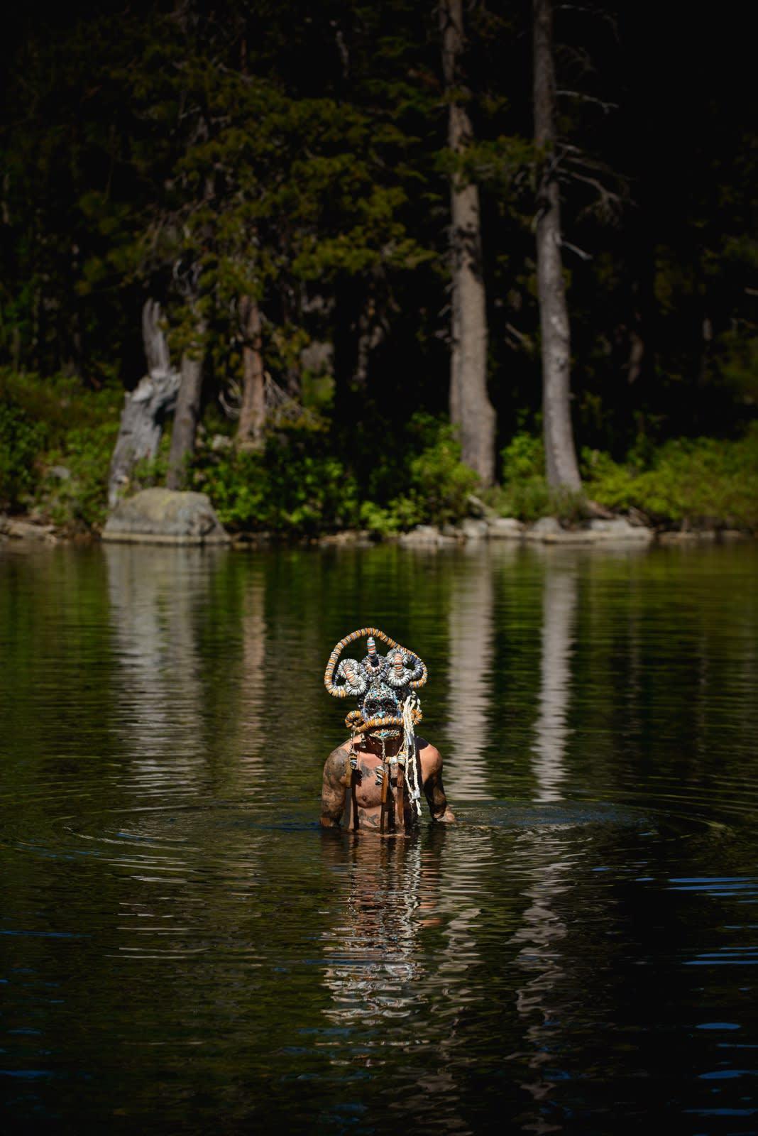 Portrait of artist Lucien Shapiro, nude in Mt. Shasta lake wearing ornate mask