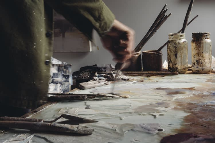 Artist Kim Cogan mixing paints in his studio