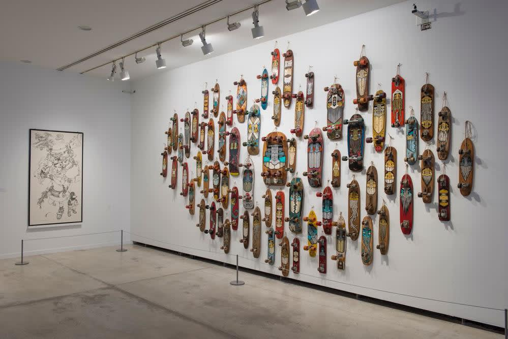 Installation view of GATS show, featuring dozens of painted vintage skateboards