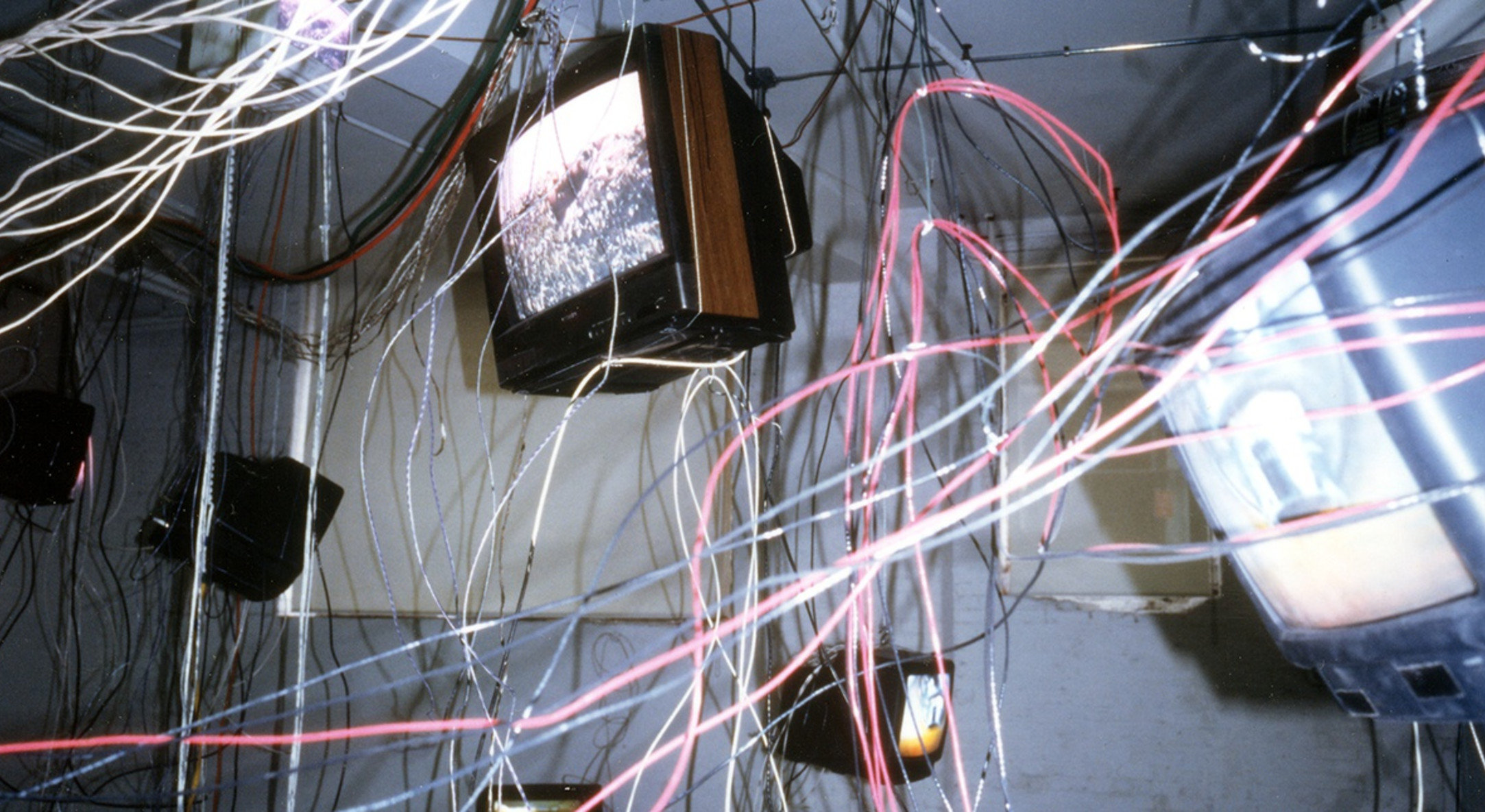 Carolee Schneemann, More Wrong Things, 2001, Fourteen video monitors with video loops suspended from the ceiling within an extended tangle of wires, cables, and cords, Dimensions vary with installation
