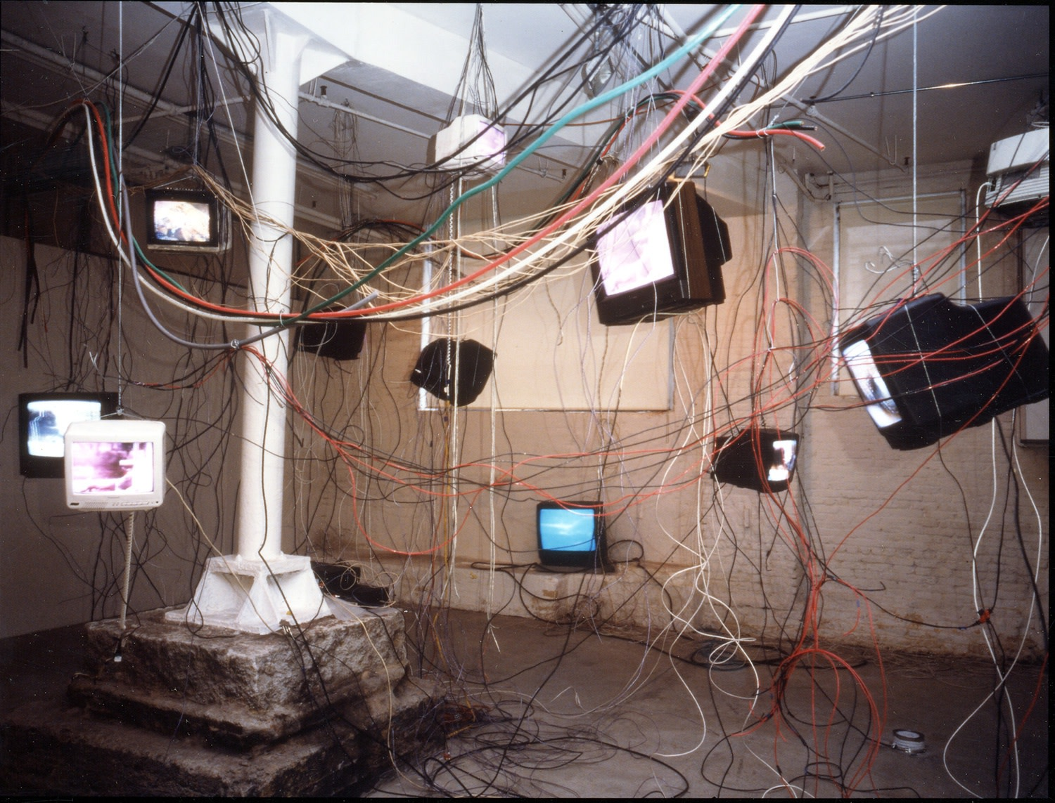 Carolee Schneemann More Wrong Things, 2001 Fourteen video monitors with video loops suspended from the ceiling within an extended tangle...