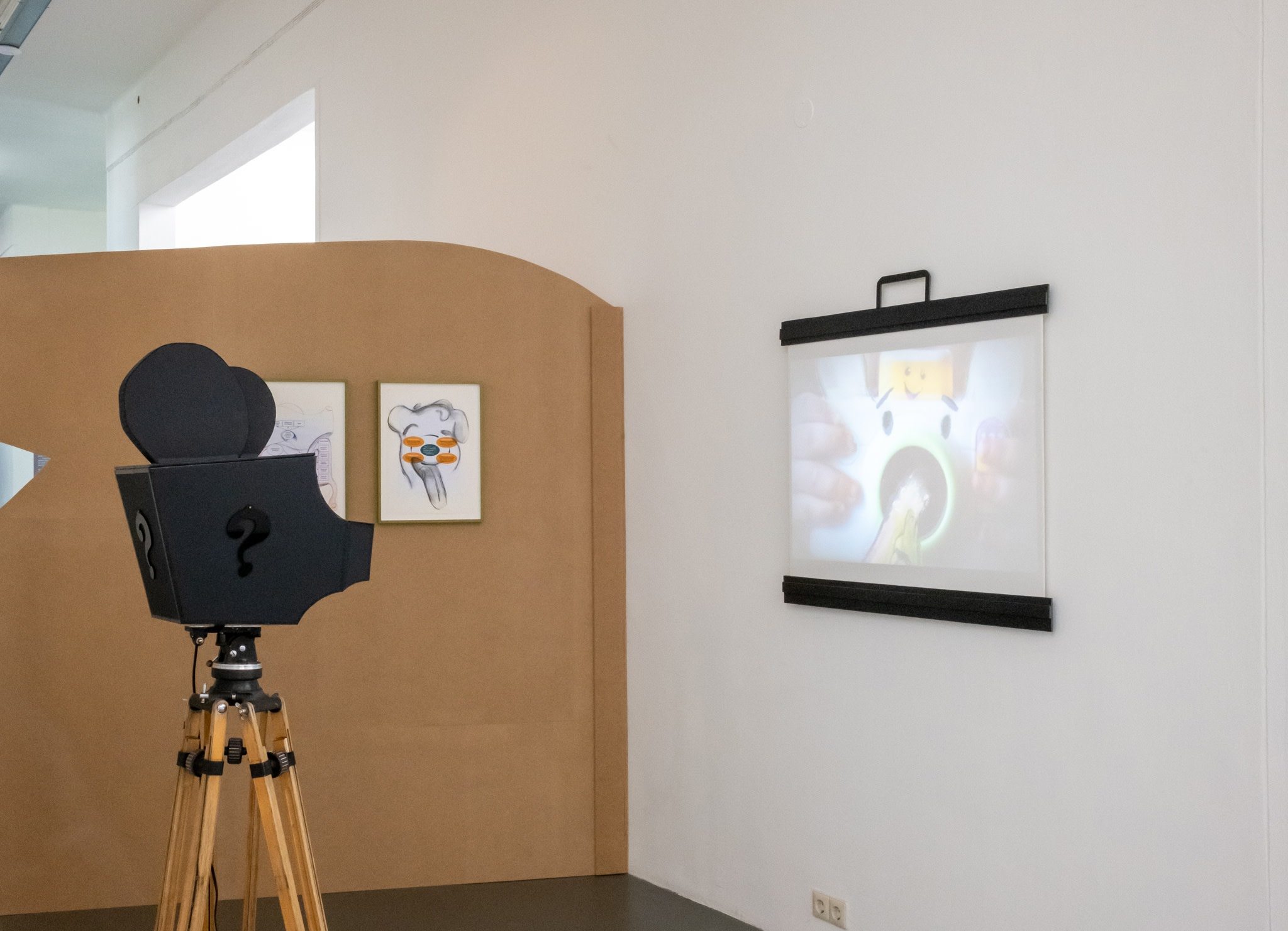 Who's Childhood?, 2021. sculptural installation, cardboard, electrical tape, Plexiglas, antique tripod, projector, projection screen, 164 x 73 x 73 cm (64 5/8 x 28 3/4 x 28 3/4 in) (projector on tripod), variable edition of 3. Photo © Jeroen Lavèn