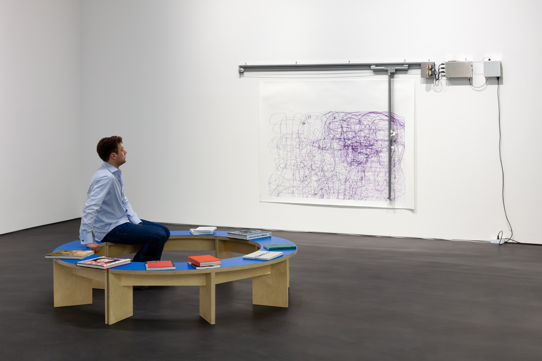 Background: Angela Bulloch, Dynamic Stereo Drawing Machine, 2020, sound-activated drawing machine, ink, metal rails and electronic motor, paper, 170 x 300 cm (170 x 300 x 66 7/8 in) approx. Foreground: Liam Gillick, Prototype Seating For A Revised Production Centre, 2005, plywood, paint, 50 x ø 200 cm (19 3/4 x ø 78 3/4 in). Photo © Andrea Rossetti