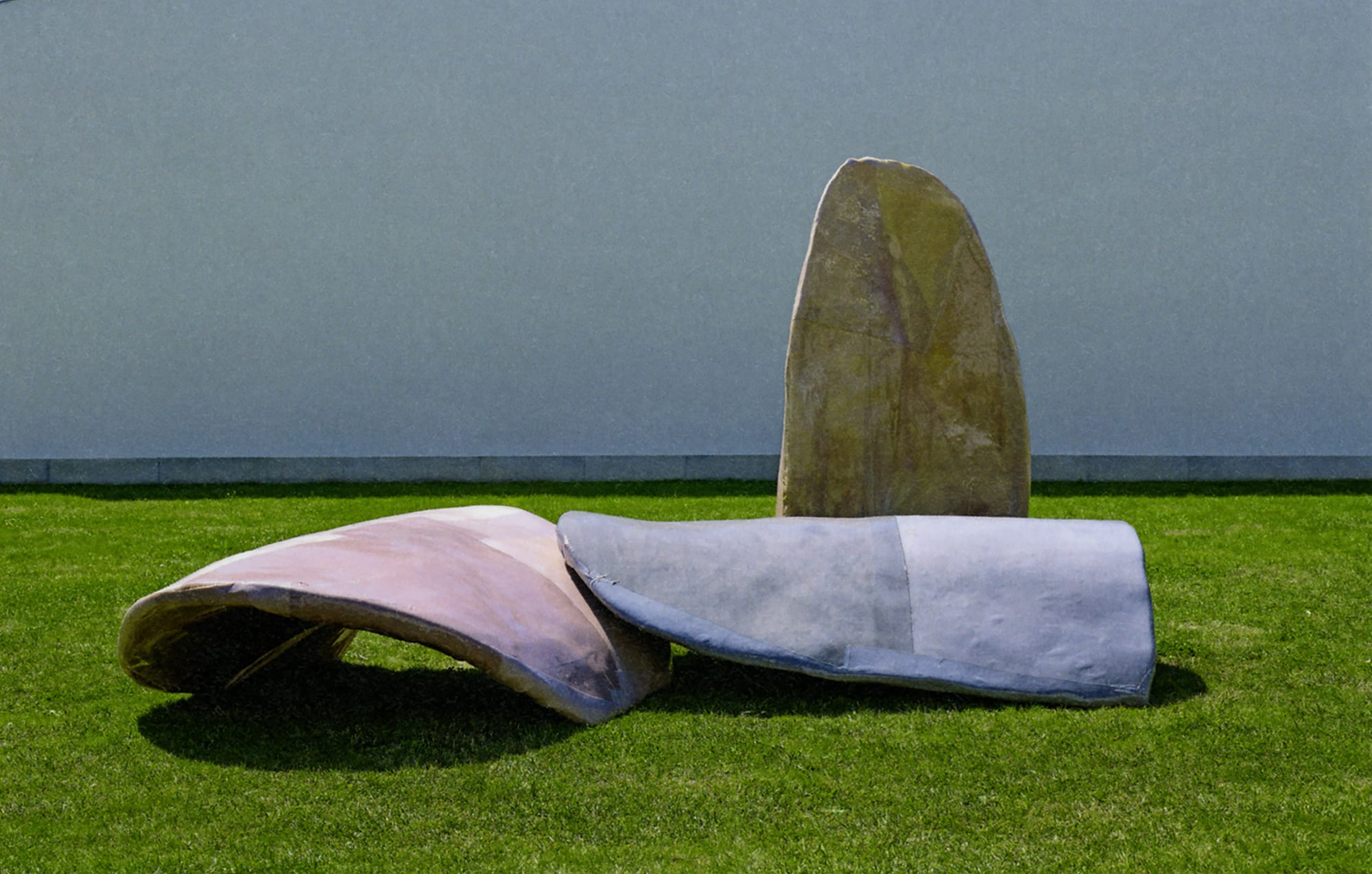 Outdoor installation of three large abstract sculptures in red, blue and yellow on a grass lawn.