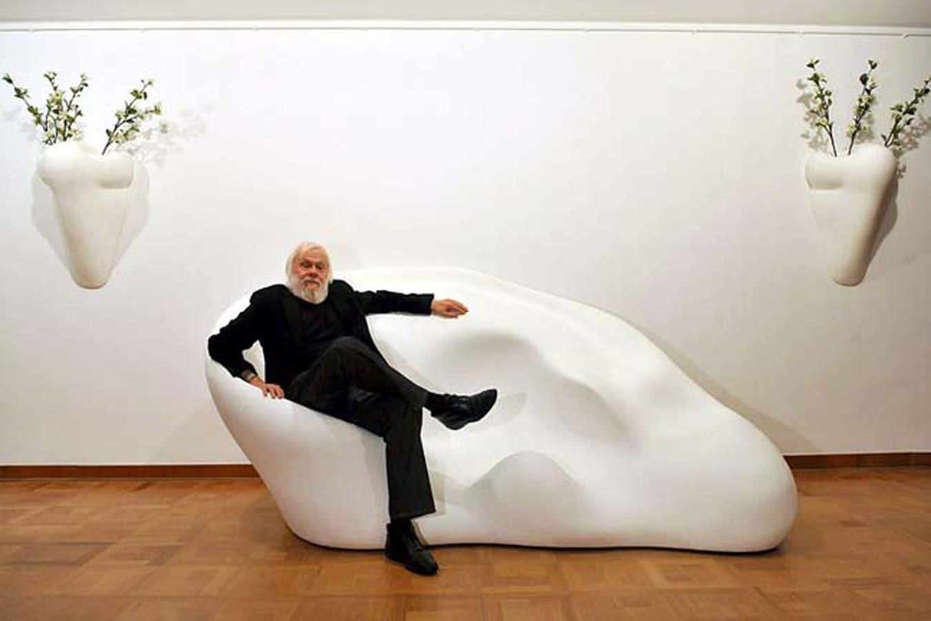 John Baldessari sitting on a sculptural form