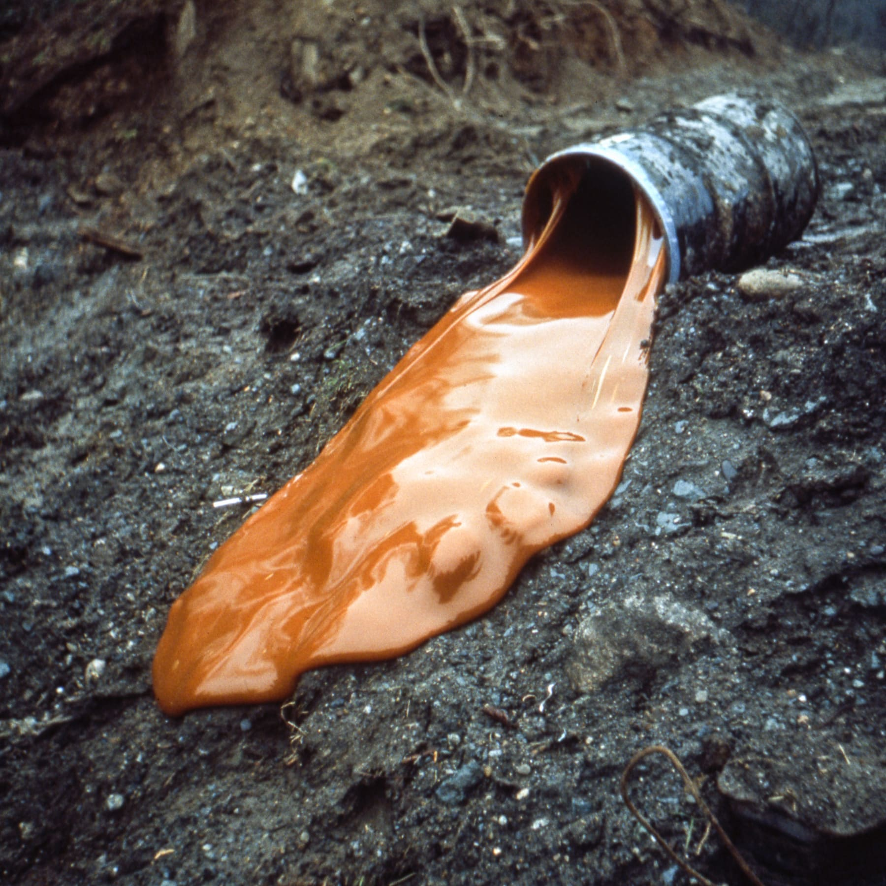 An image containing a large drum of glue at the crest of a hill and a tipped container. Earthwork by Robert Smithson