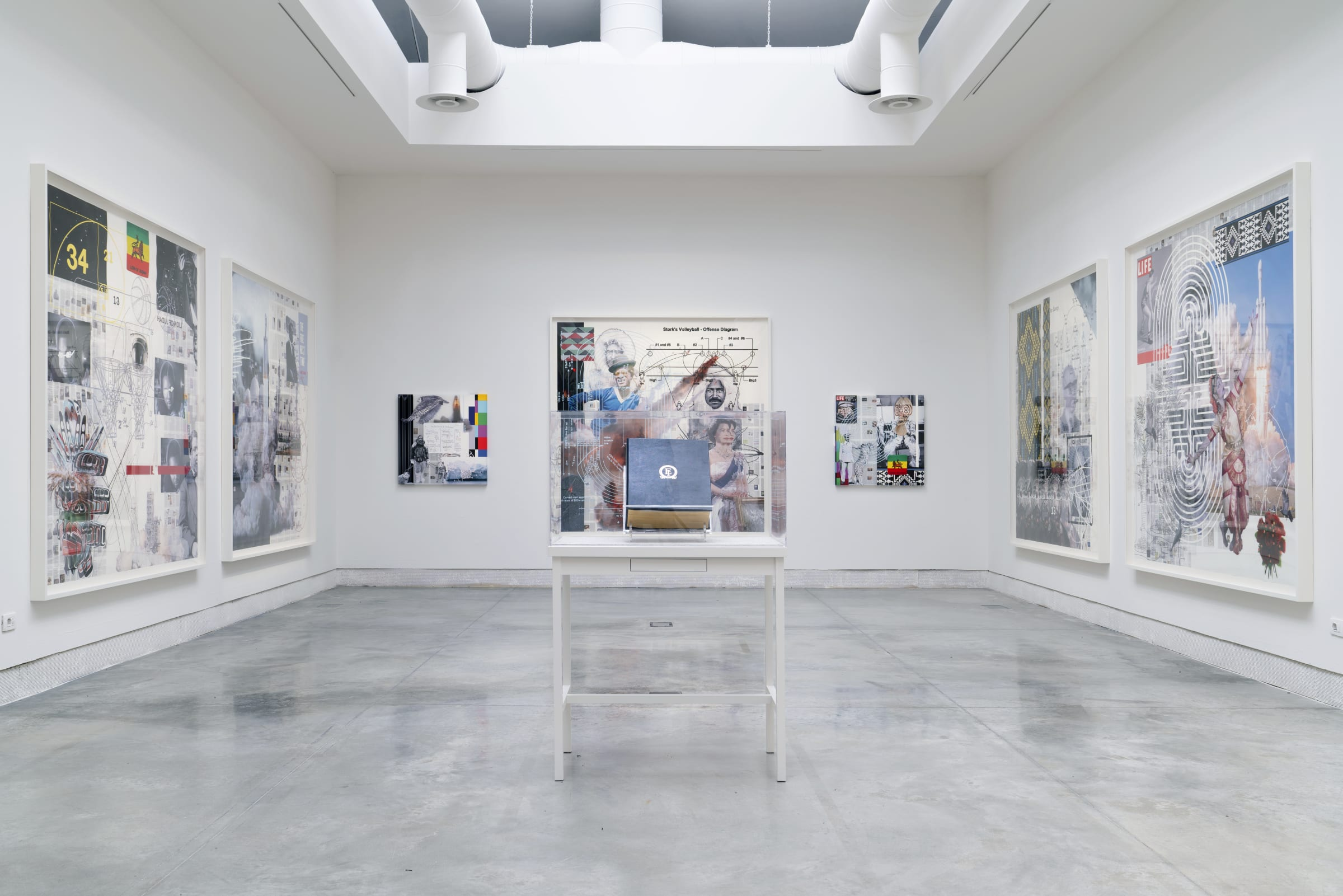 Installation view of various framed works on 3 walls with a vitrine in the center by Tavares Strachan