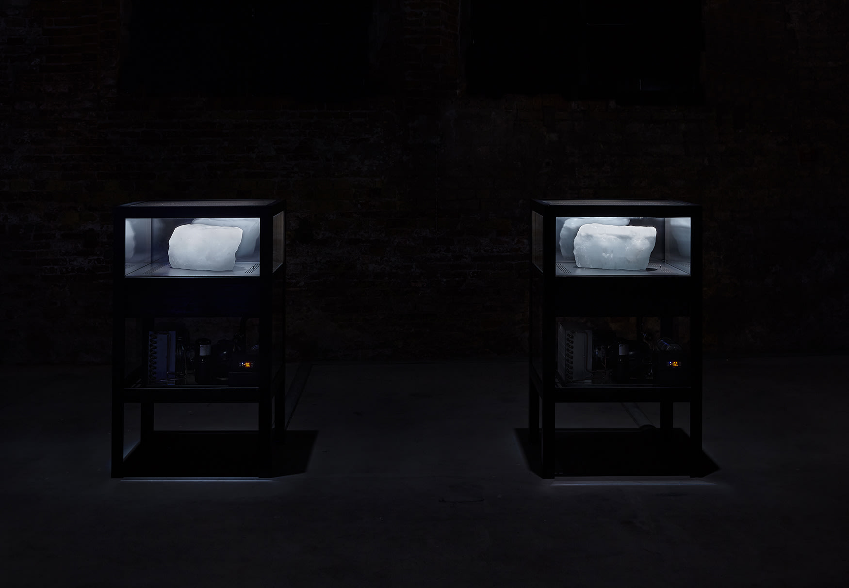 An installation view of two glass refrigerators with blocks of ice by Tavares Strachan