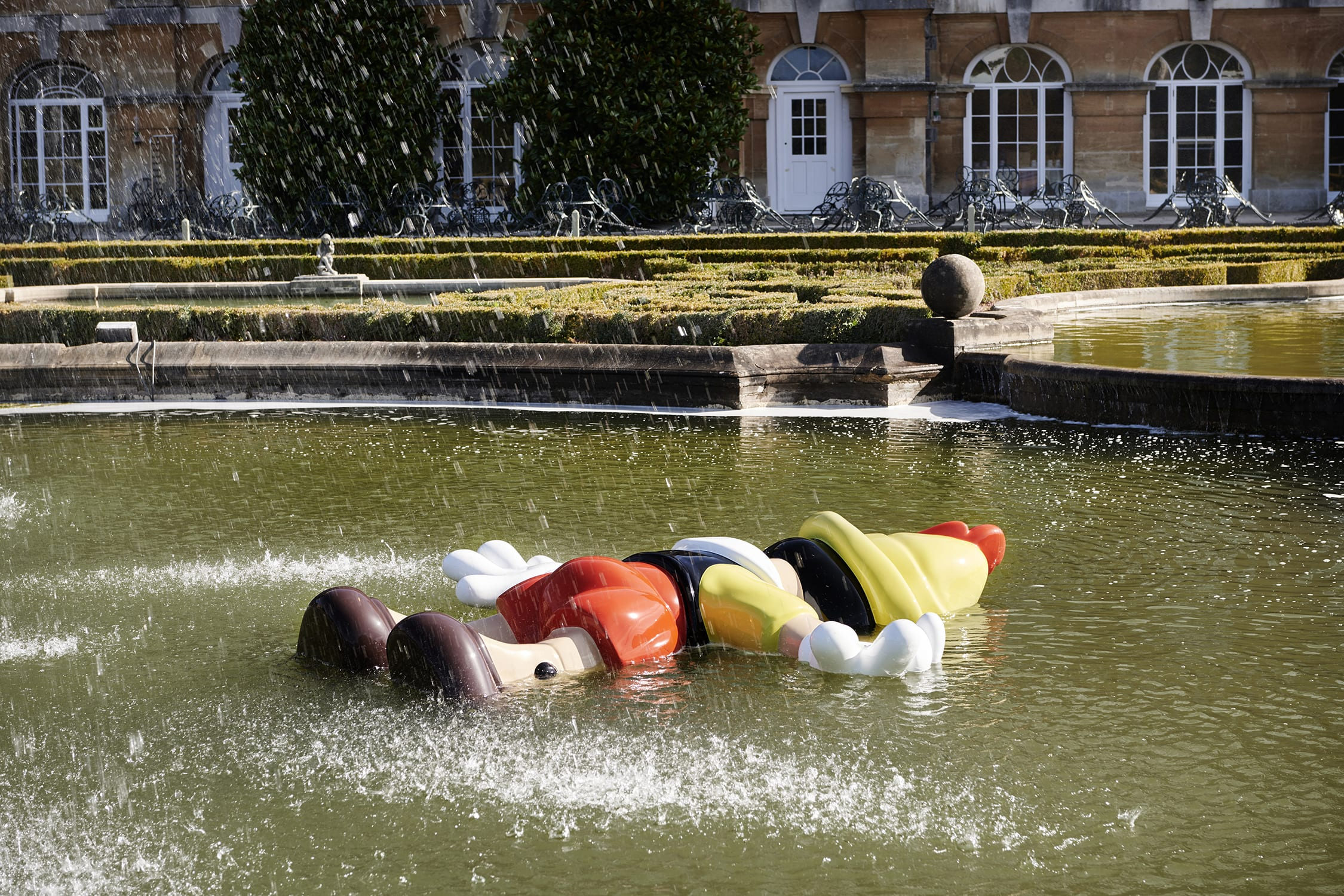 A statue of Pinocchio laying face-down in a fountain
