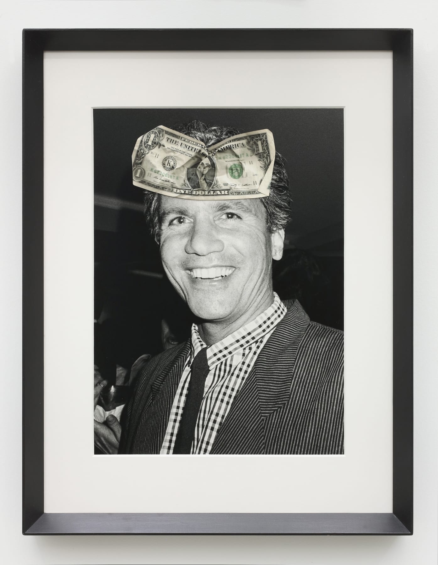 A framed black and white photograph of a man with a dollar bill attached to the image on his forehead