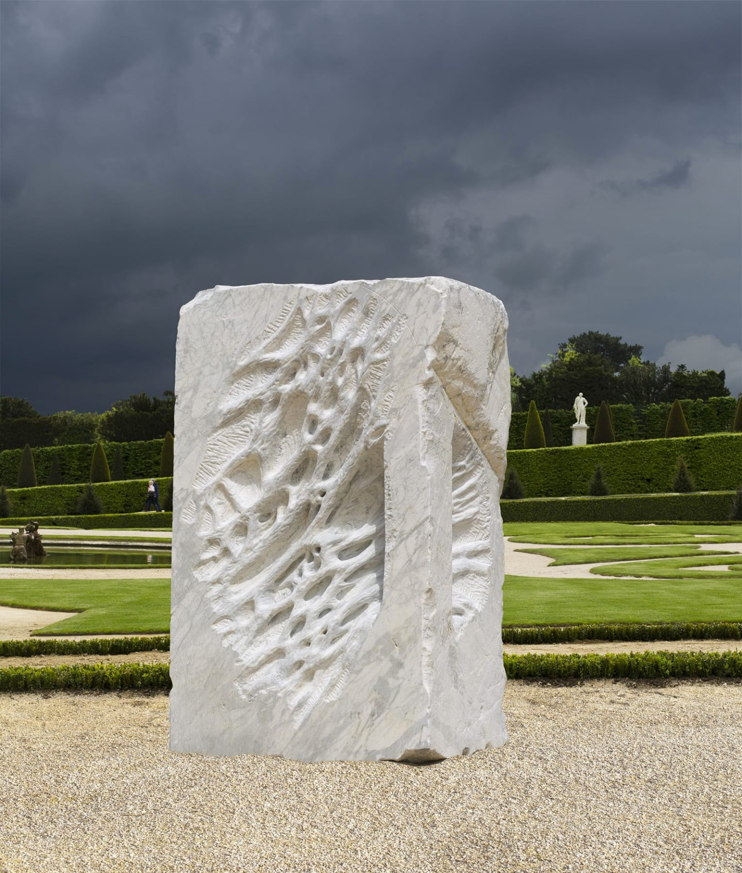a large grey, carved slab of stone by Giuseppe Penone displayed in a park