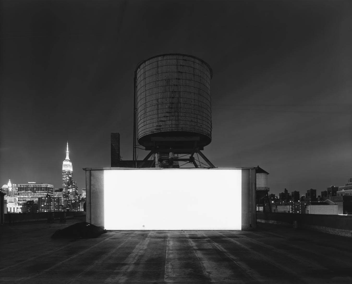 A rectangle of light is projected onto a wall below a water tower. There is a city skyline in the background.