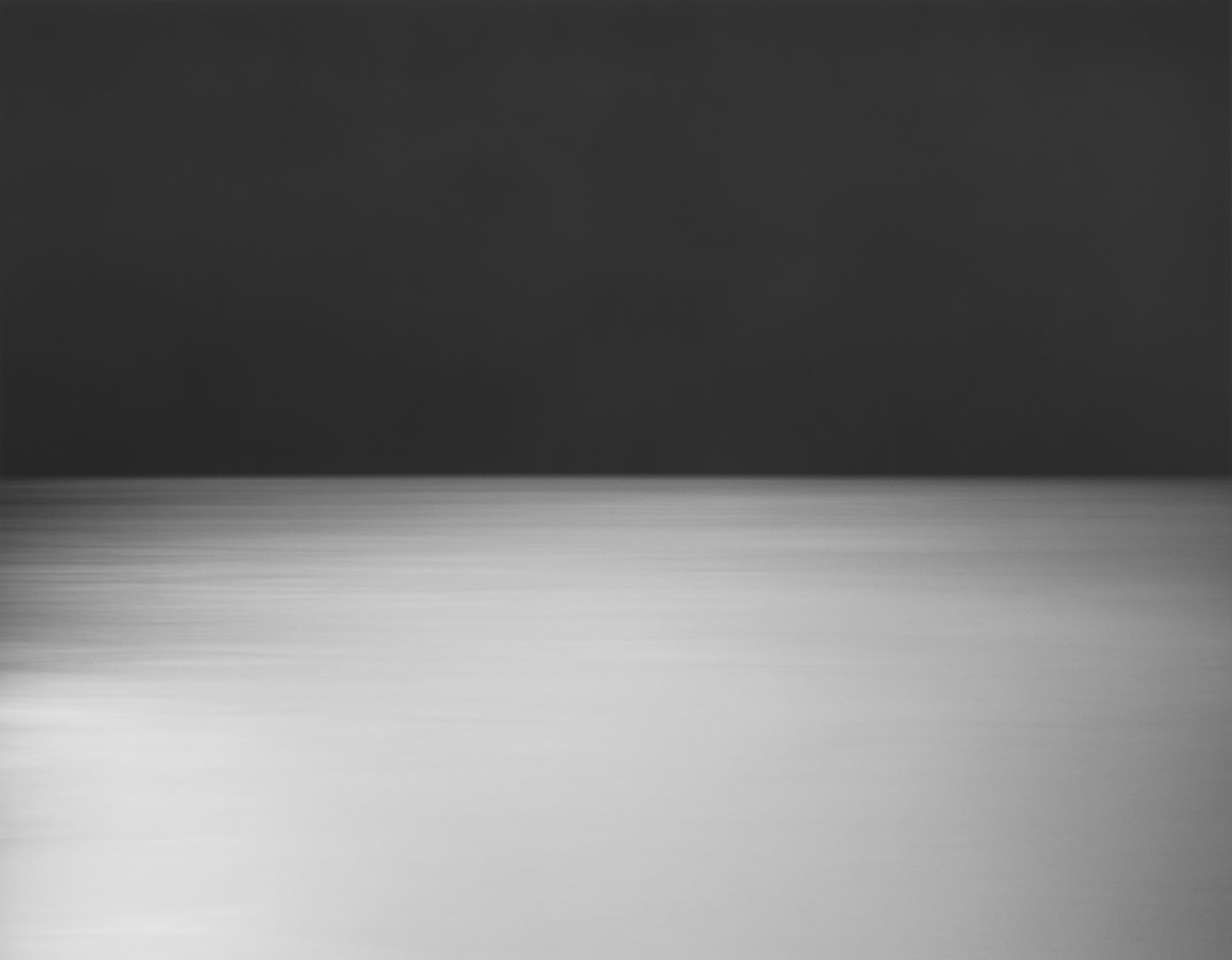 A grayscale image of a horizon line with a dark sky and lighter ground.