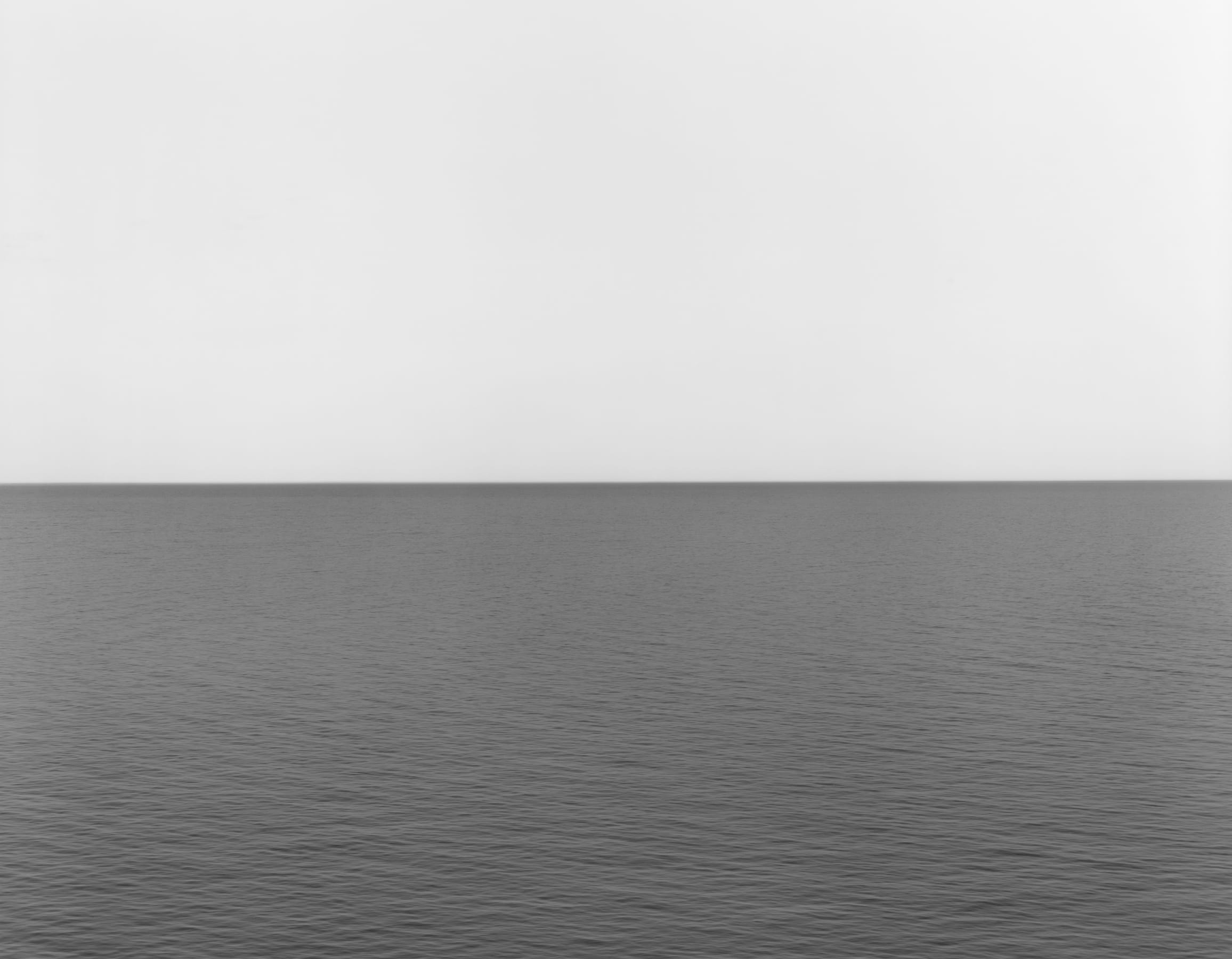 A horizon line equally divides the frame between a light gray sky and darker body of calm water.
