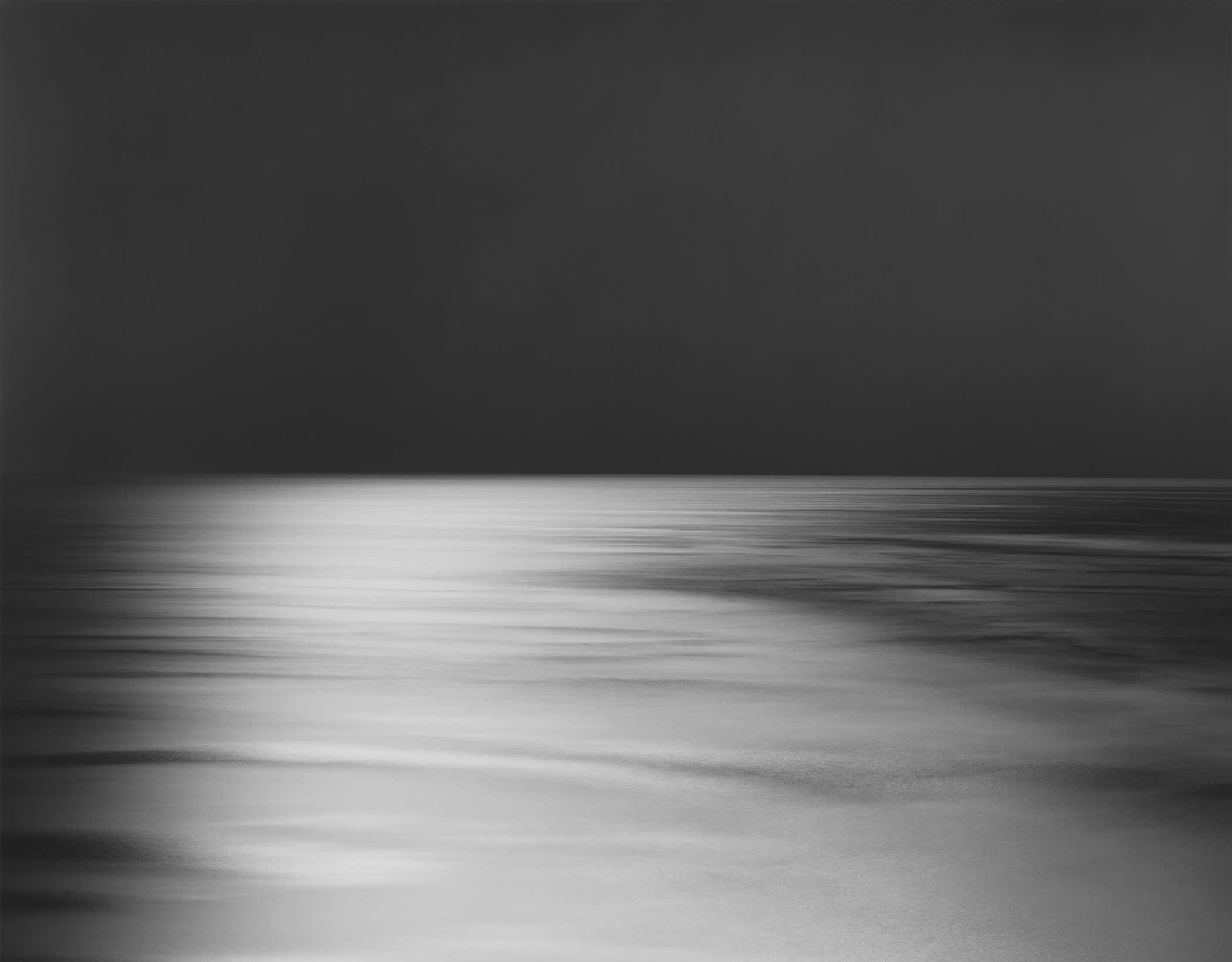 A Hiroshi Sugimoto photograph: A grayscale image of a horizon line with a dark sky and lighter ground.