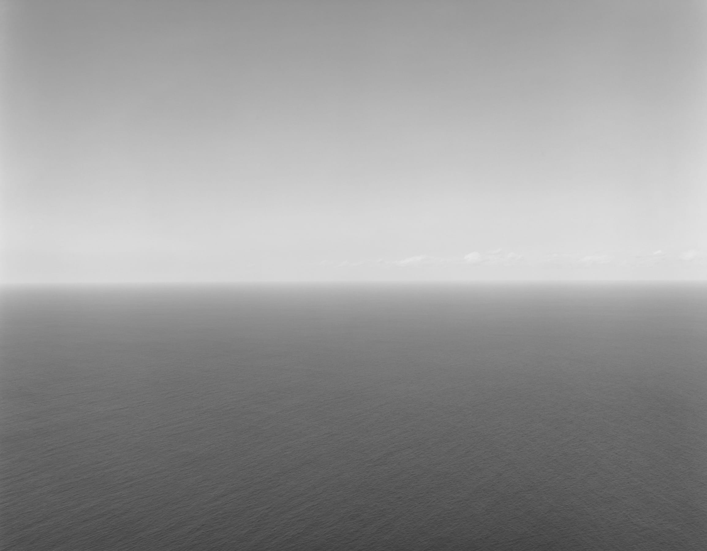 A Hiroshi Sugimoto photograph: A horizon line equally divides the frame between a light gray sky and darker body of calm water.