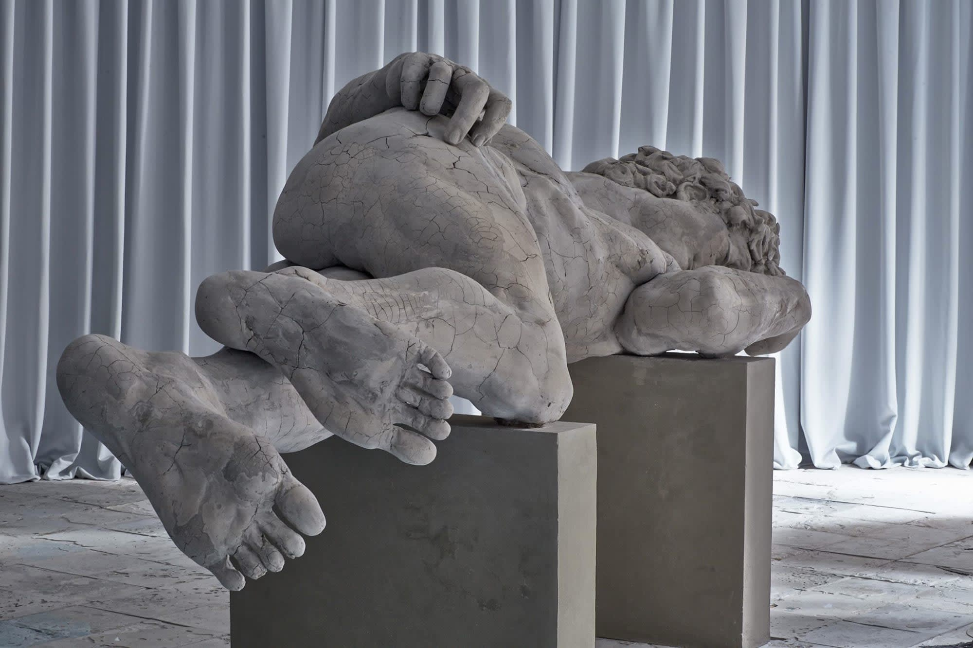 Gallery view of figurative marble sculpture sleeping on two uneven cement pillars. The figure is cracked.
