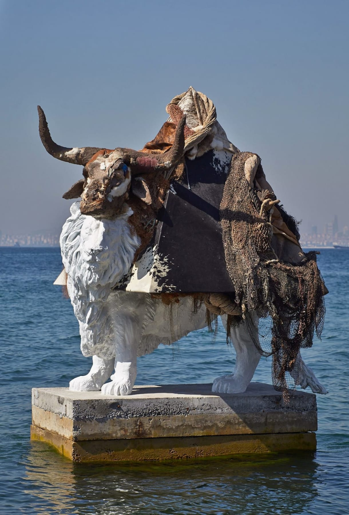 Classical lion sculpture on a pedestal in a body of water is covered with an antlered animal skull, netting, and tribal blankets