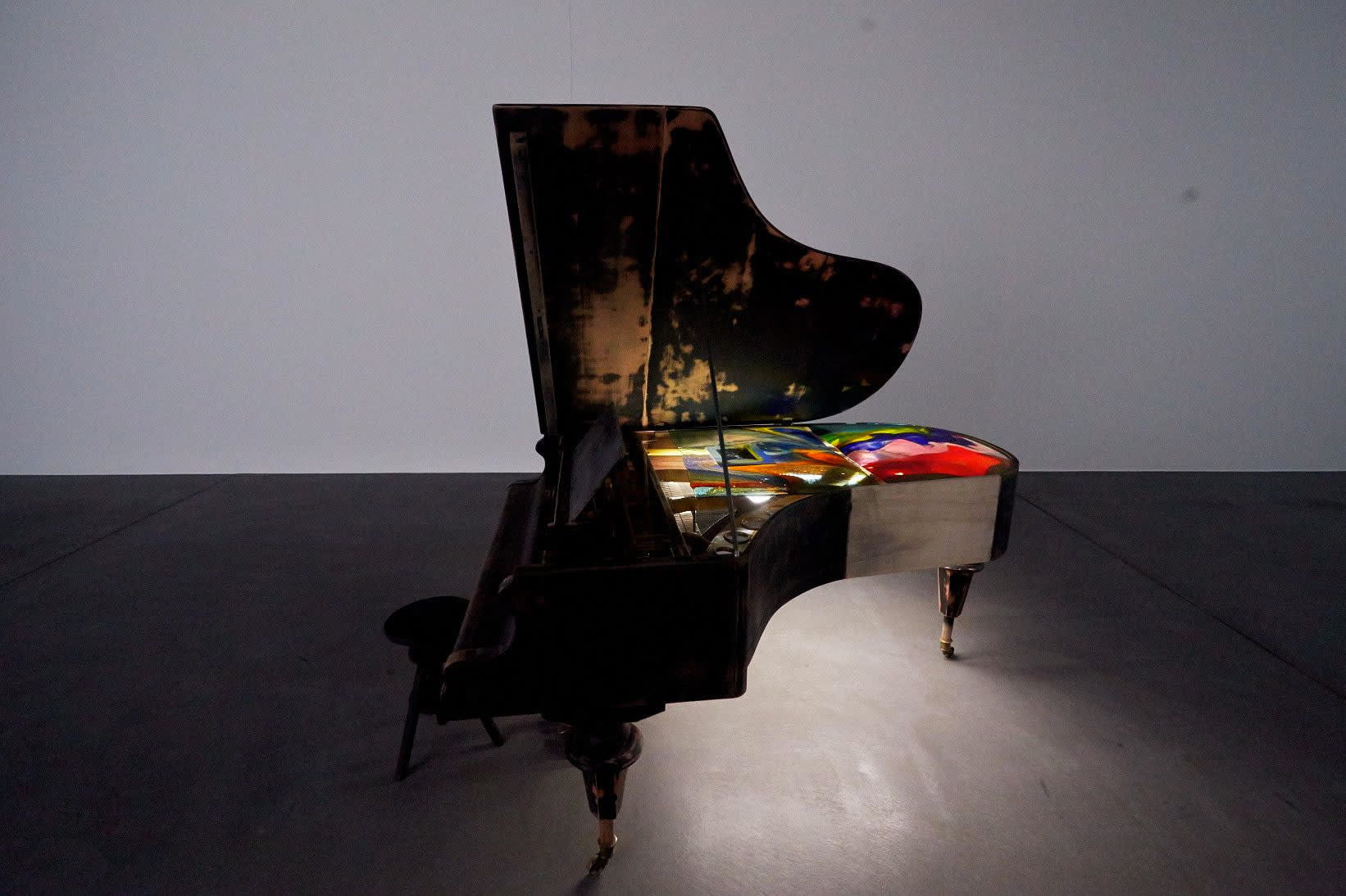Installation of piano. Inside of piano is painted in multiple colored amorphous shapes.