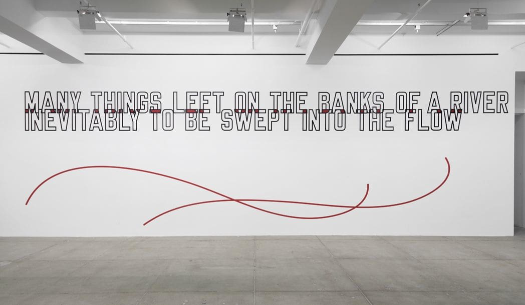 "Gallery installation of wall text ""MANY THINGS LEFT ON THE BANKS OF A RIVER INEVITABLY TO BE SWEPT INTO THE FLOW"" above two red intertwining swirling lines."