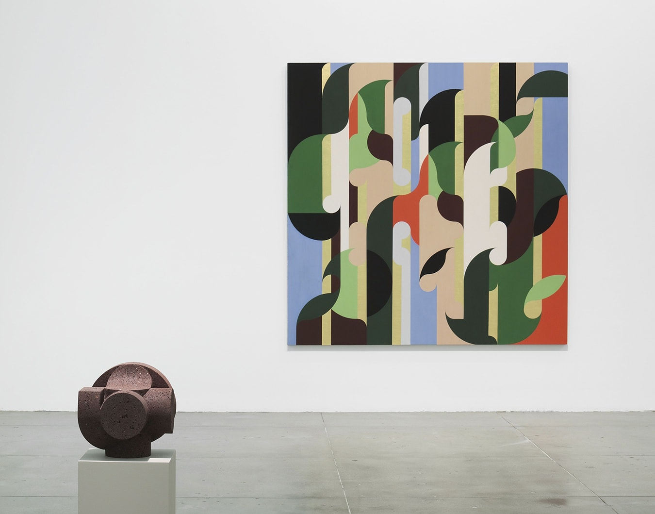 A stone sculpture in front of an abstract painting.