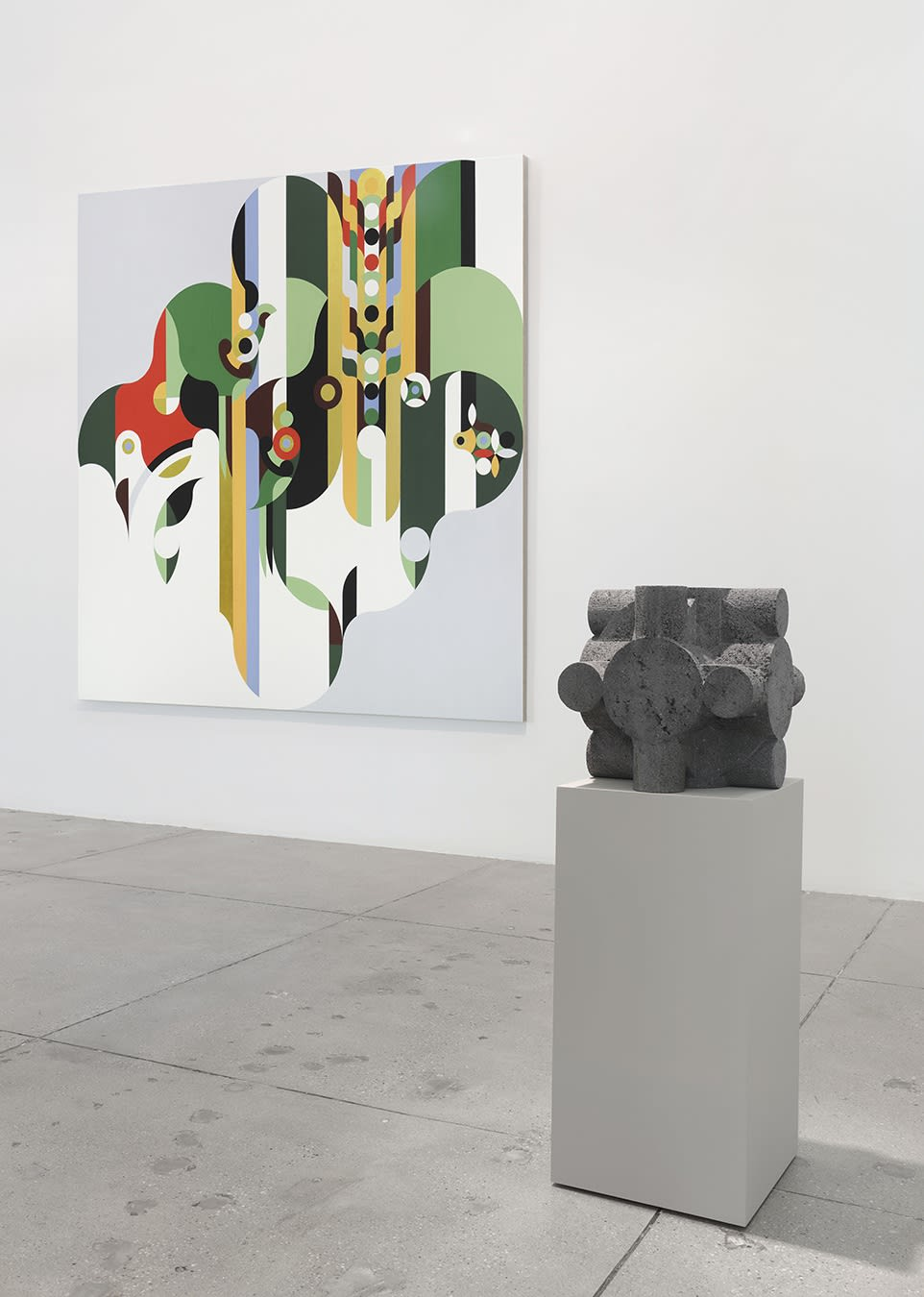 A small stone sculpture in front of an abstract, geometric painting.