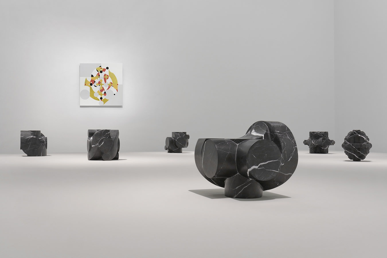6 small stone sculptures in front of a colorful abstract painting on a white wall.