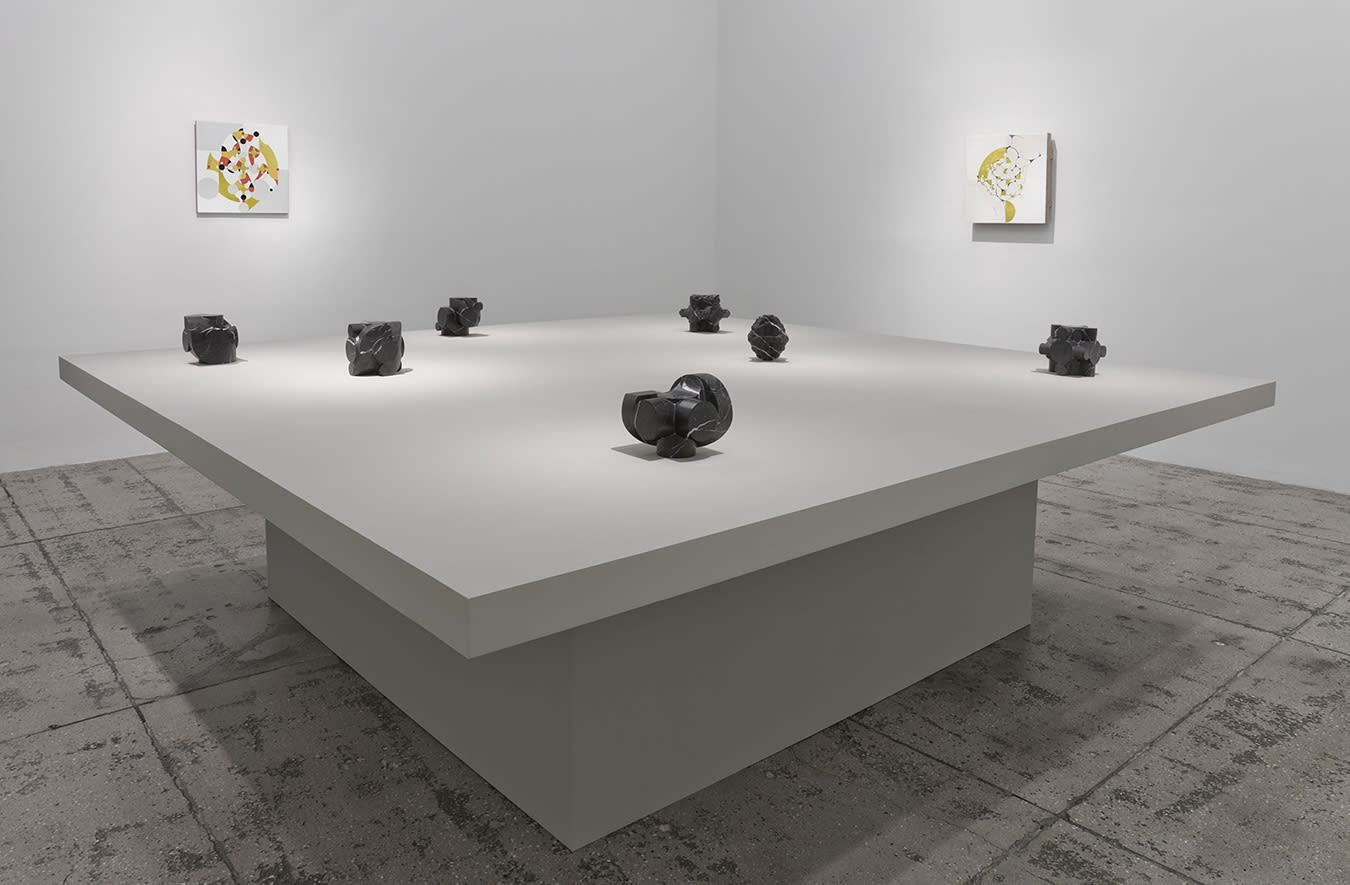 7 small stone sculptures on a table in front of two abstract paintings.
