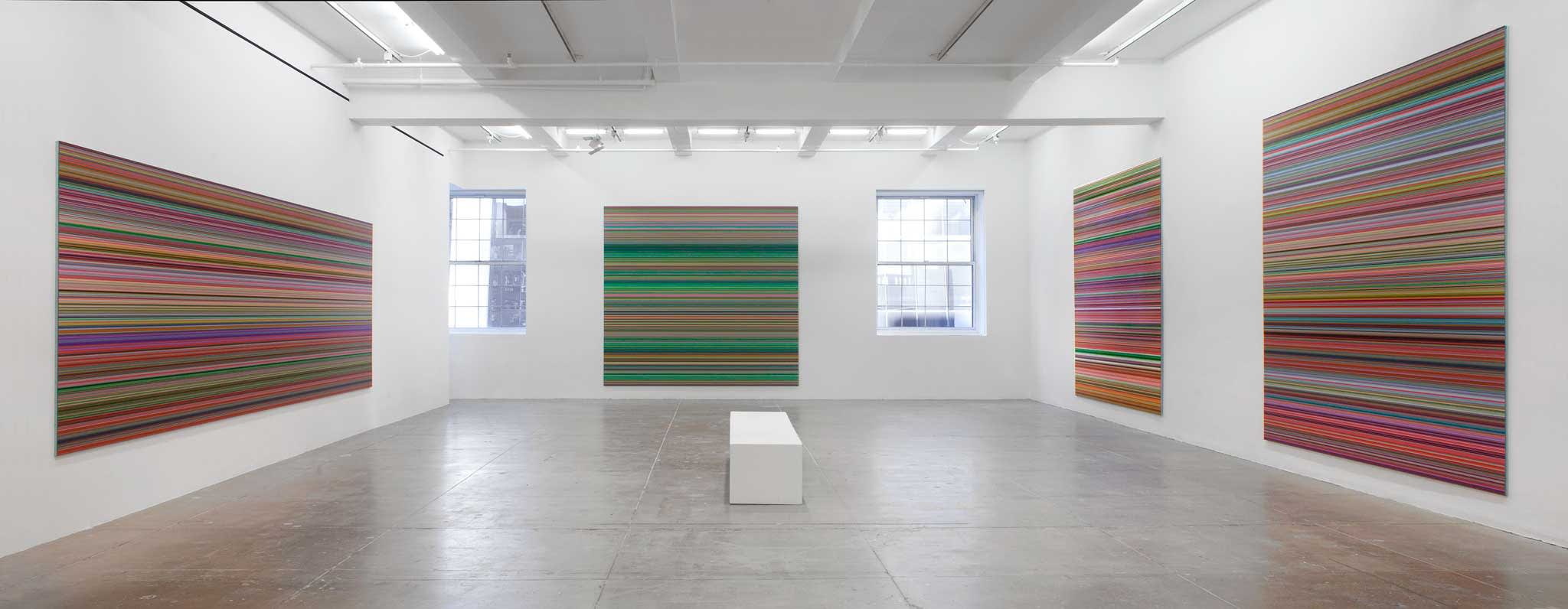 Four paintings, two on separate walls, three with a mix of primarily red vertical stripes among other colors; one with primarily green vertical stripes