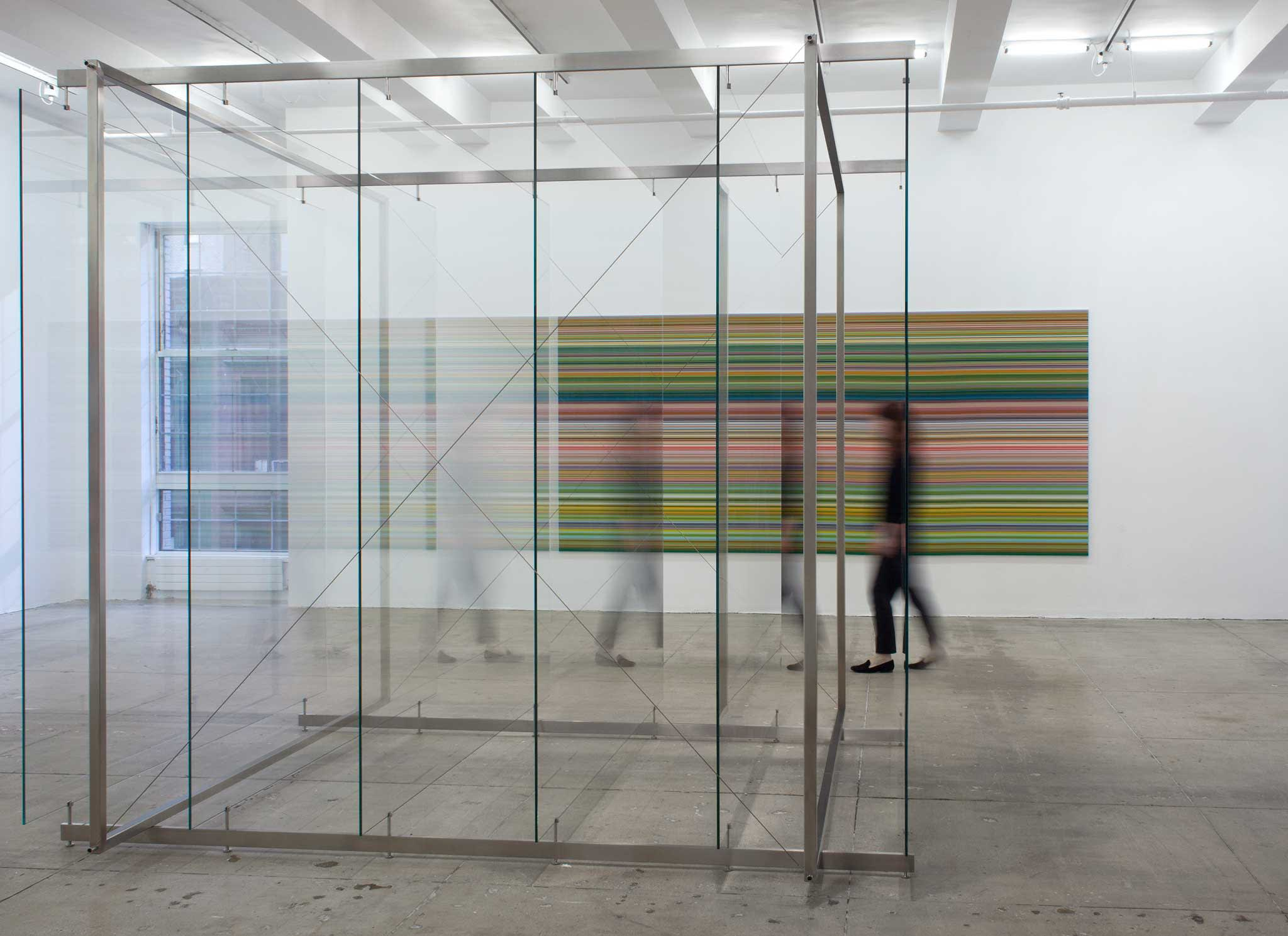 A girl walks behind a floor-to-ceiling tall sculpture made of glass and steel; behind her is a painting of yellow, green and black stripes.
